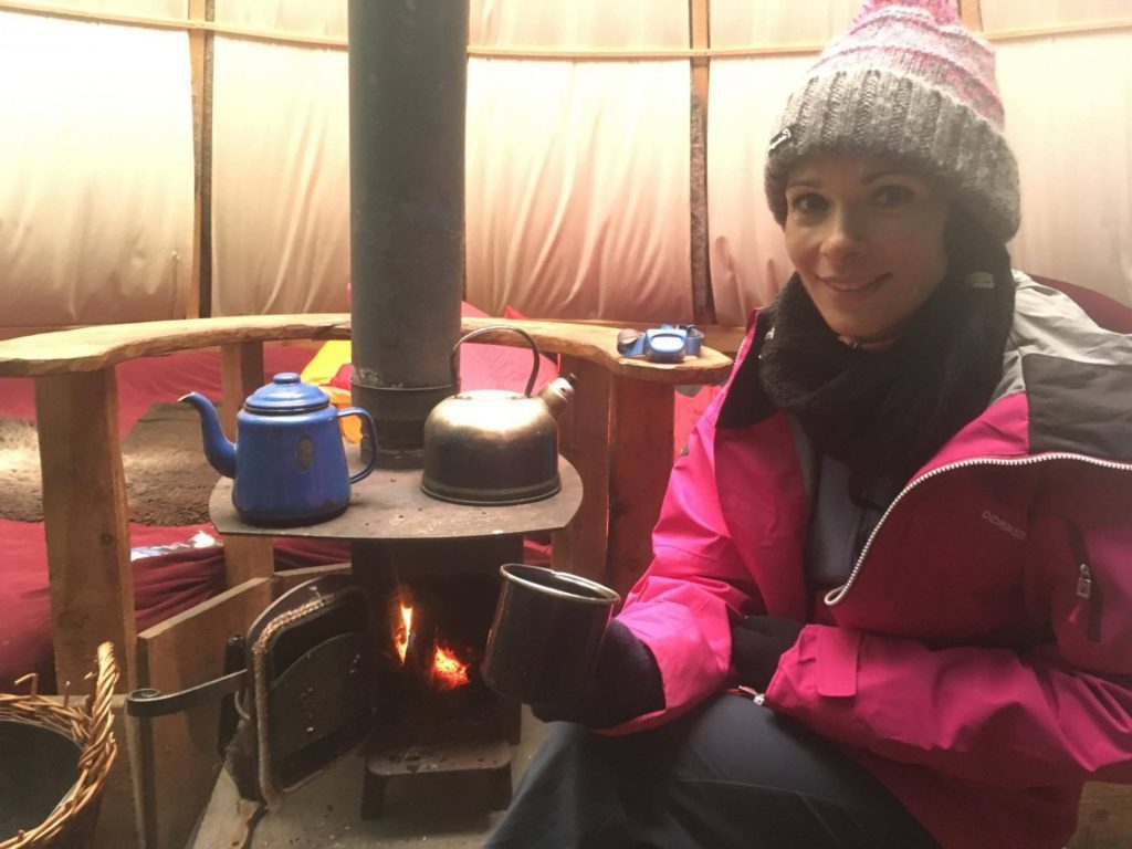 Gayle enjoys coffee inside the cosy kata's wood-burning stove.