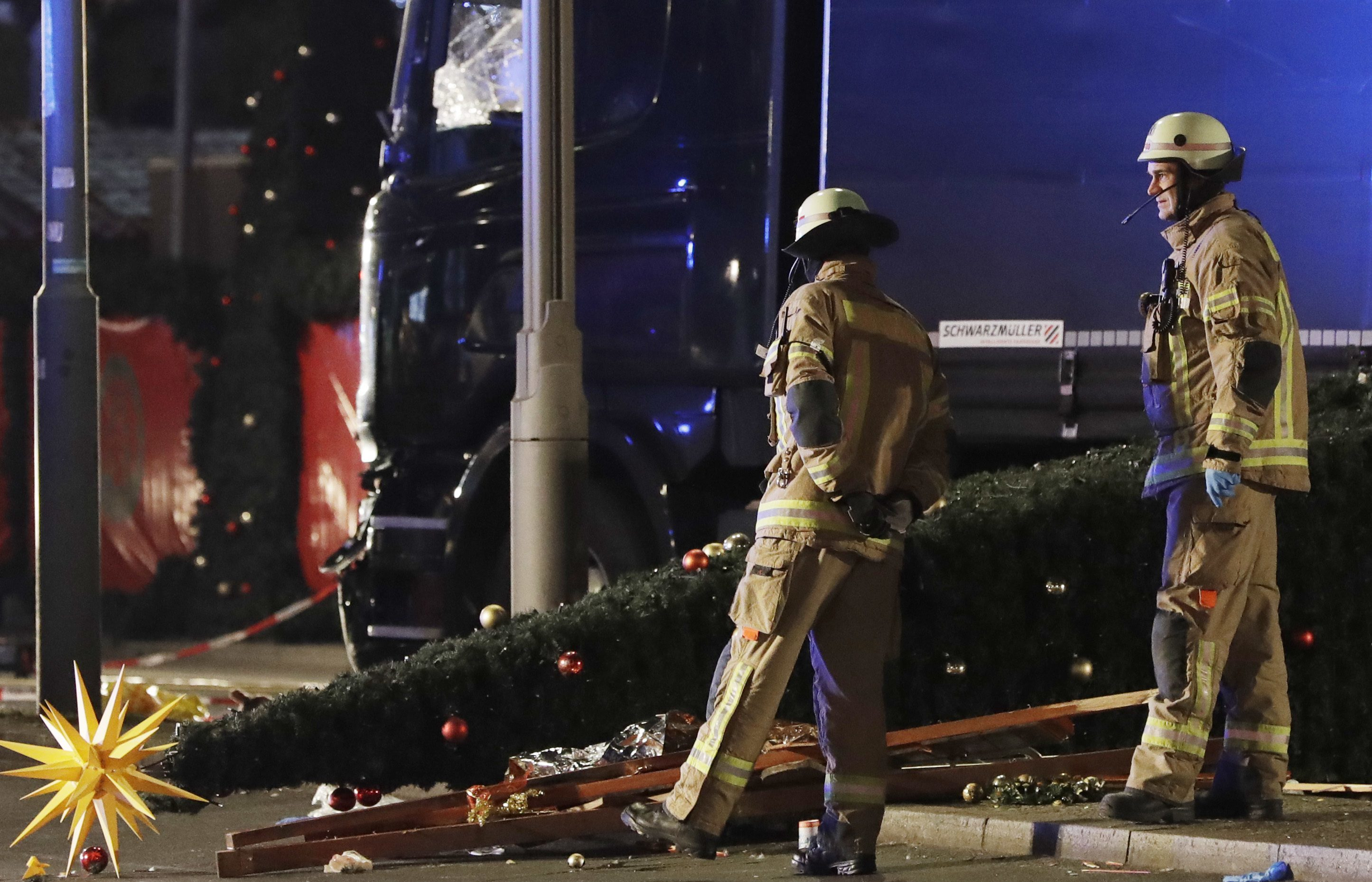 Emergency workers examine the lorry and a Christmas tree toppled by the impact.