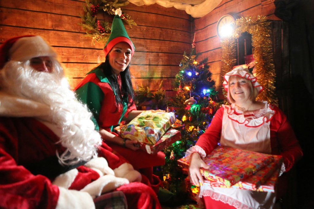 Gayle with Santa and Mrs Claus in the cosy grotto.