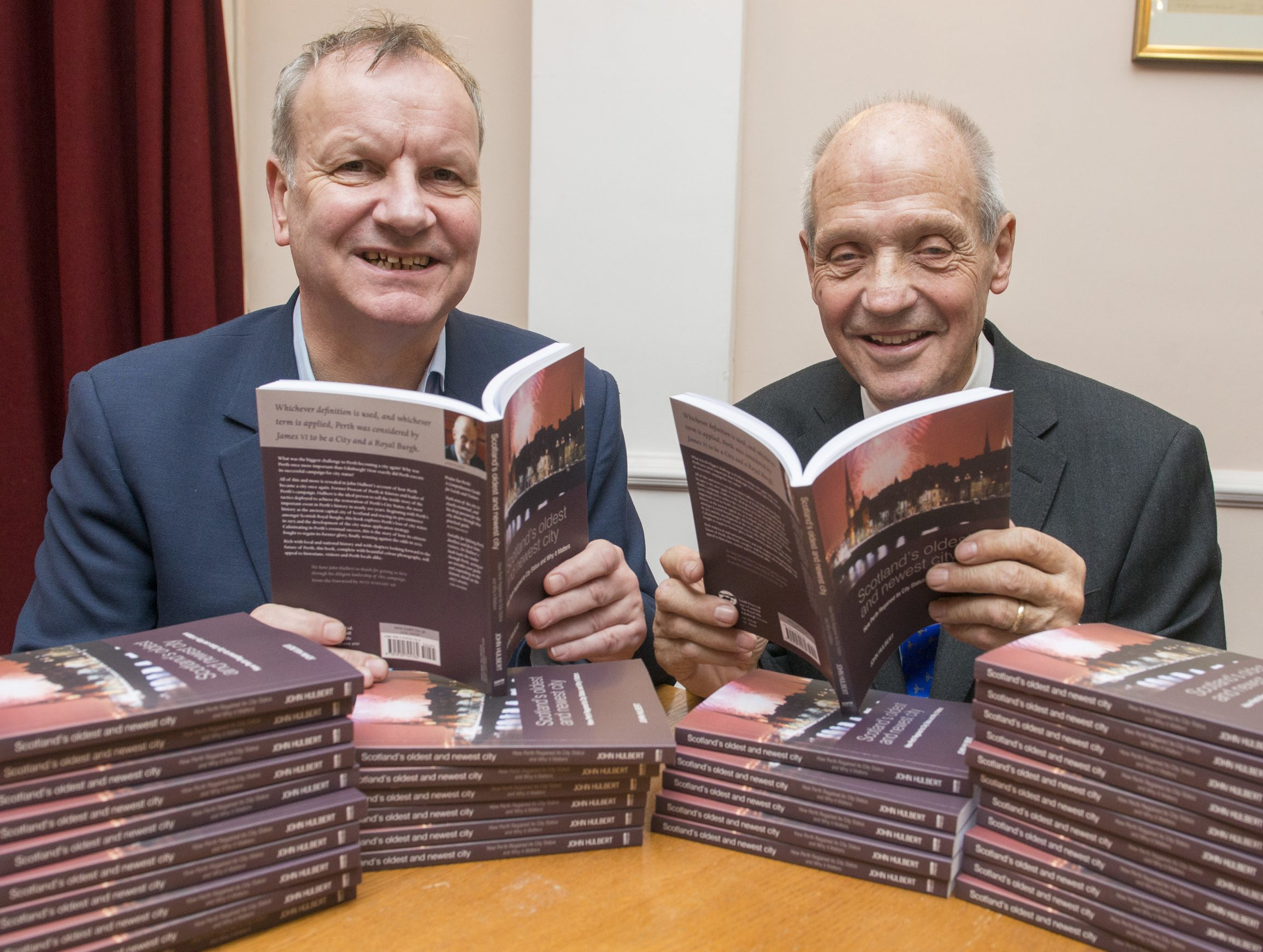 John Hulbert on the right is pictured with his new book and Pete Wishart MP.