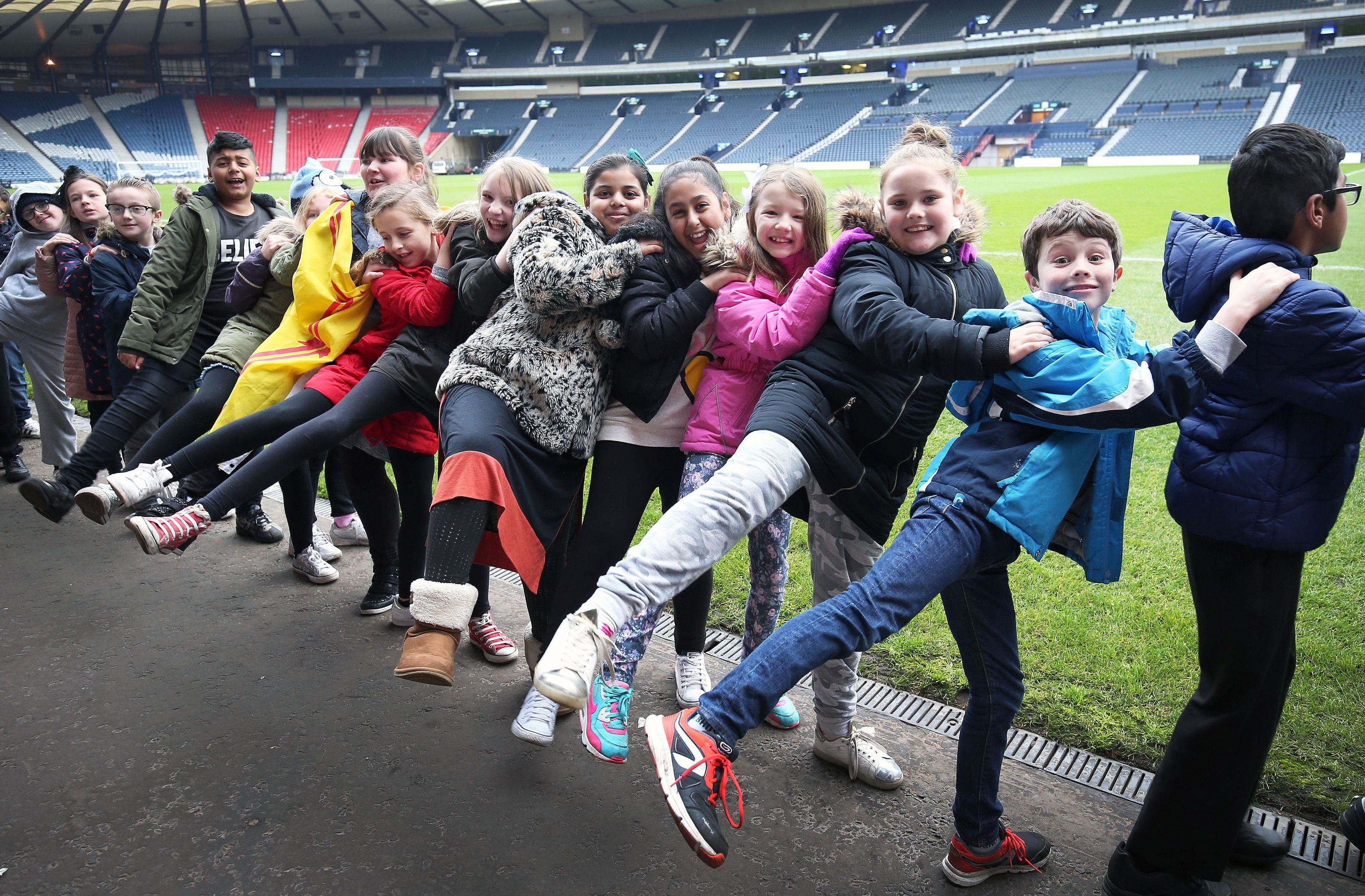Hundreds of school children, and their teachers, join a giant conga dance at Hampden Park, Glasgow, to raise funds for Glasgow the Caring City.