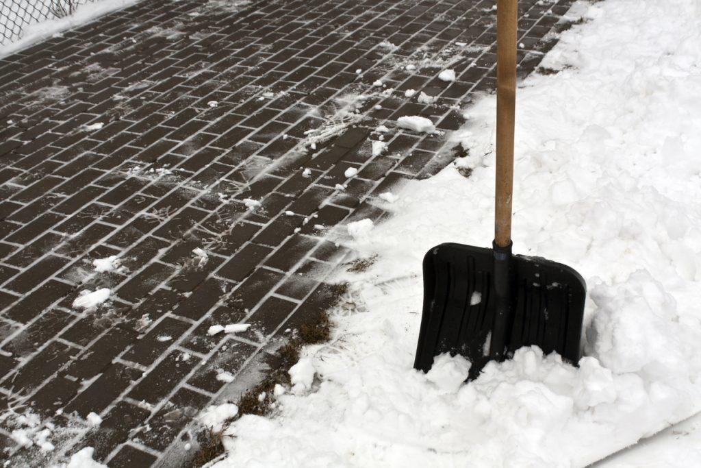Black plastic snow shovel and pavement.