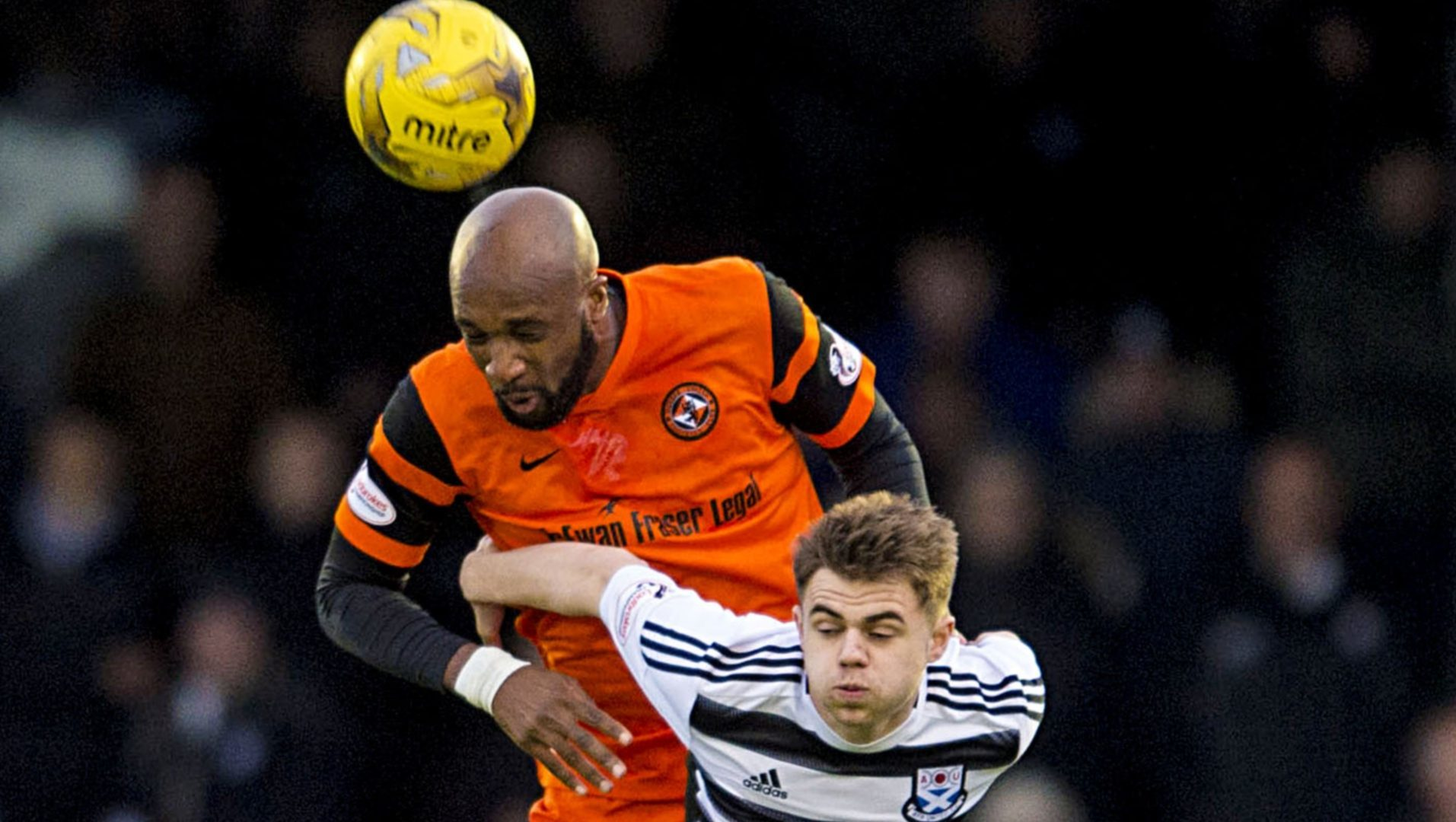 William Edjenguele beats Ayr player Alan Forrest in the air.