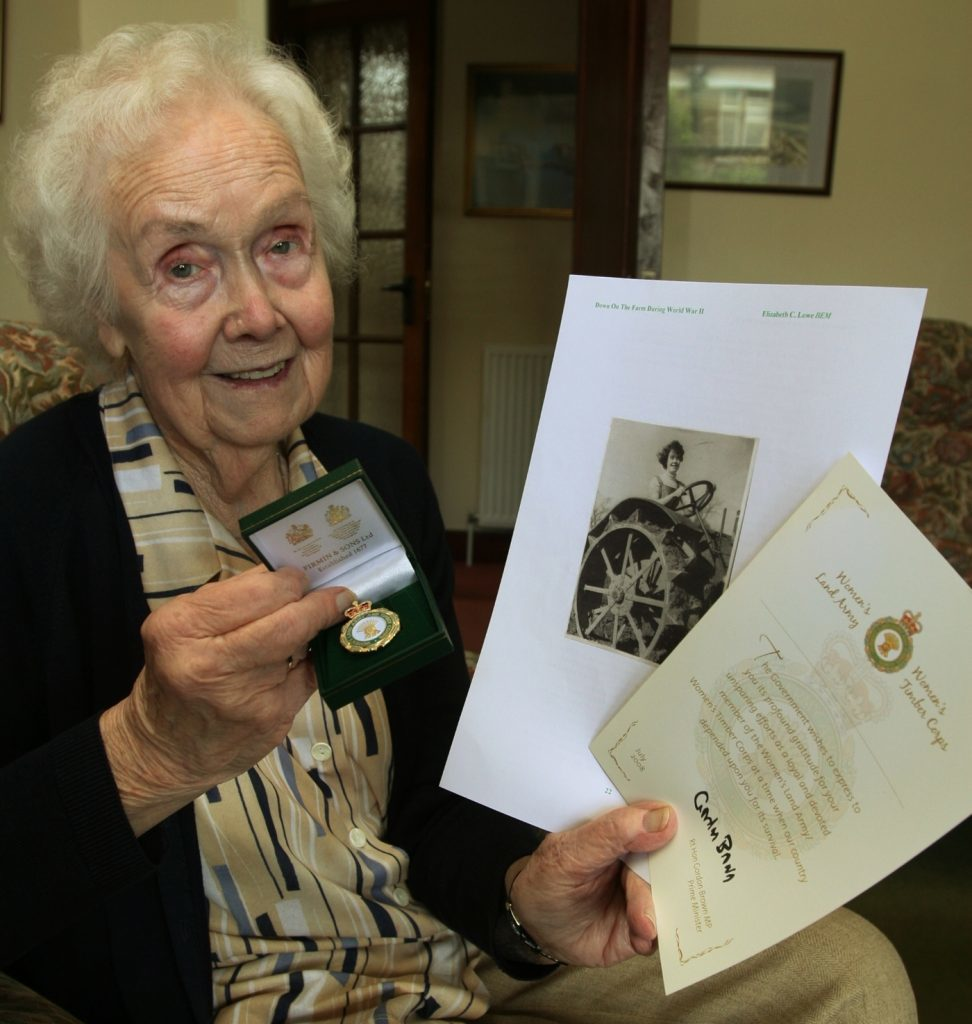 Mrs Lowe with her Land Army commemorative badge, a certificate from the then Prime Minister, and a picture of herself during her service.