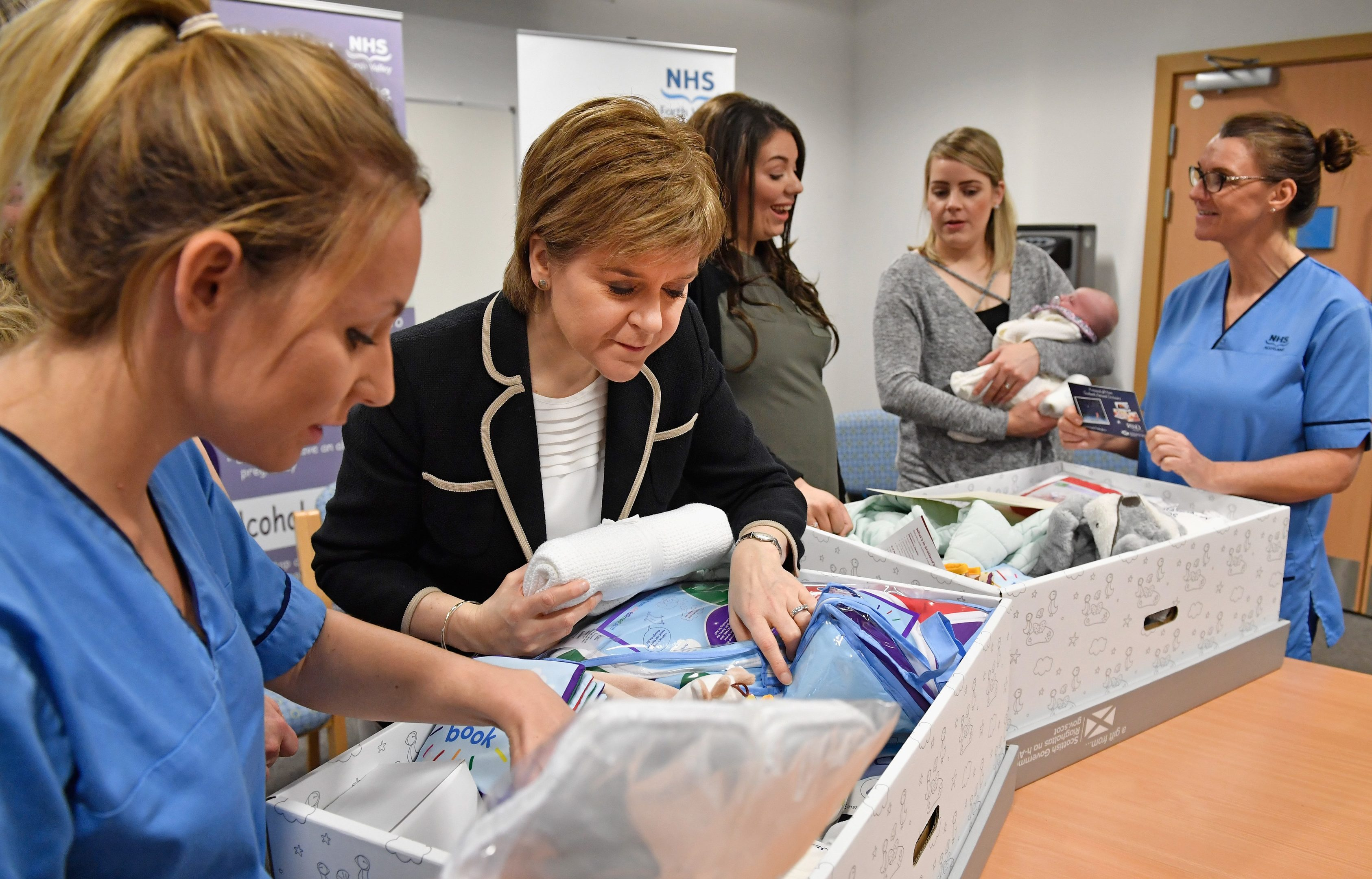 First Minister of Scotland Nicola Sturgeon meets with midwife Rachel Boyland, Toni Akande, Gail and Libby Mellor and midwife Sheila Lannon as she gives out Scotland's first baby boxes at Clackmannanshire Community Health Centre