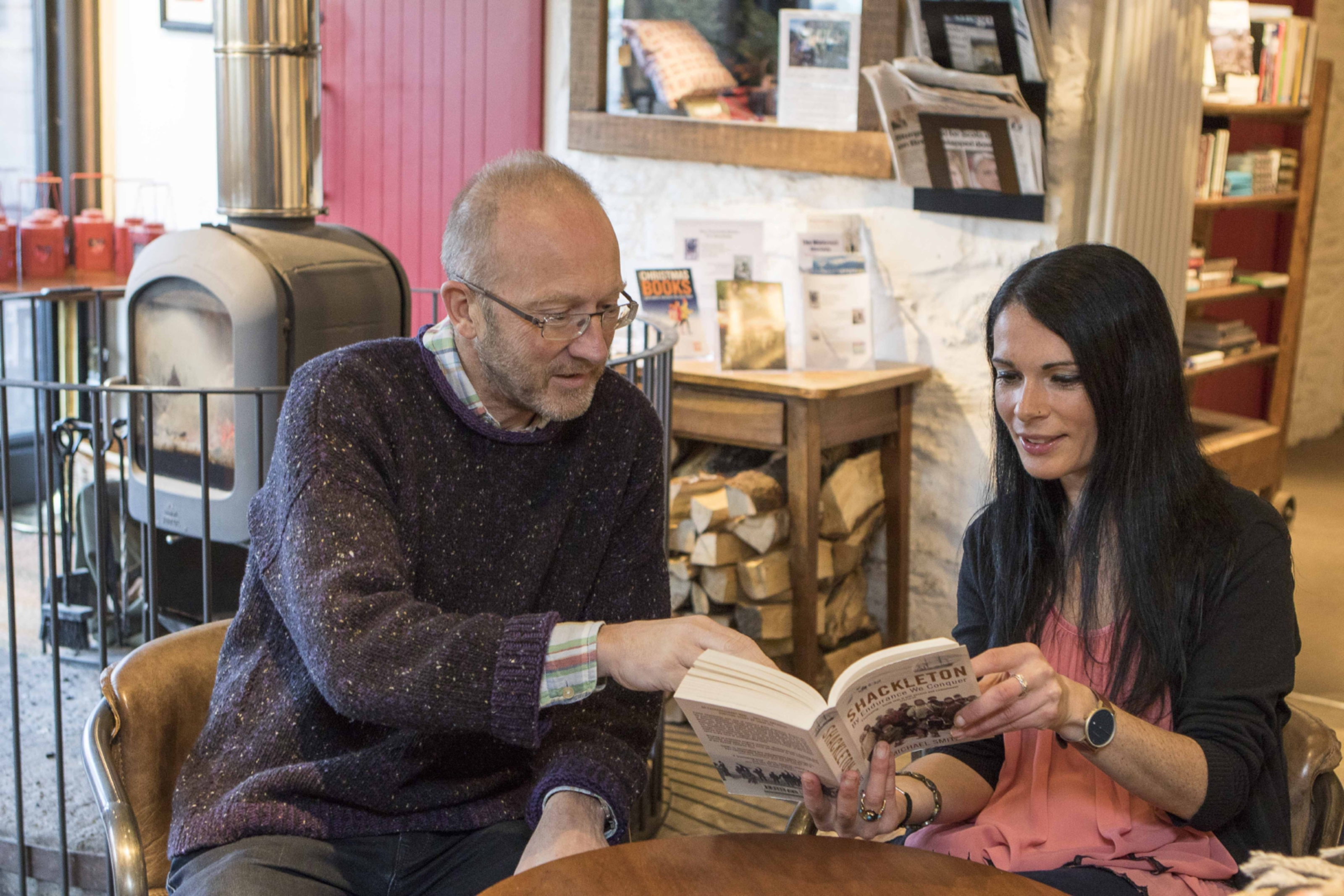 Kevin Ramage, owner of The Watermill, shows Gayle one of the shop's many books.