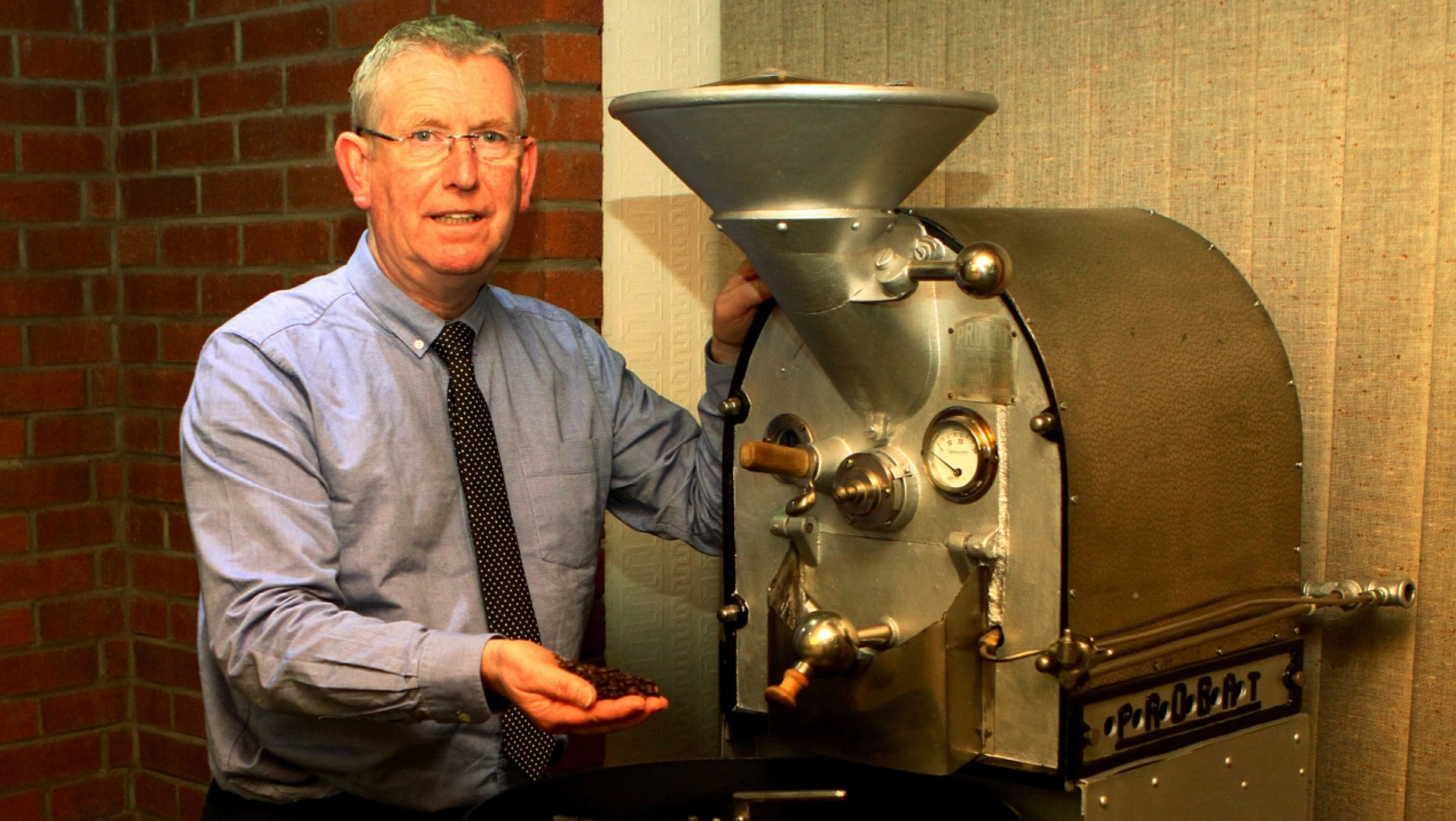 Eric Duncan, managing director of James Aimer, beside a coffee roaster from 1939.