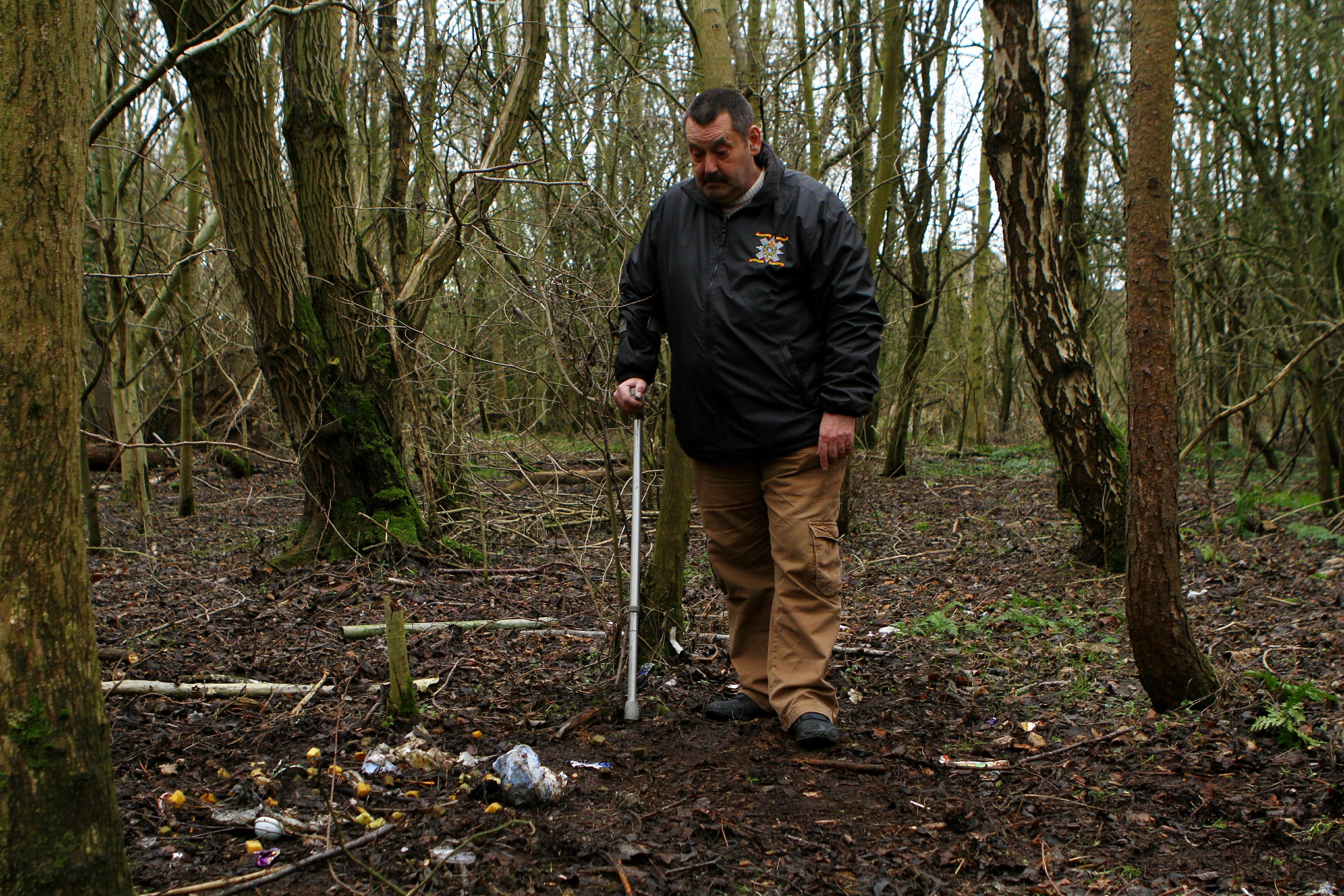 Mr Scobie examines the flytipping in the woodland near Brodie Court.