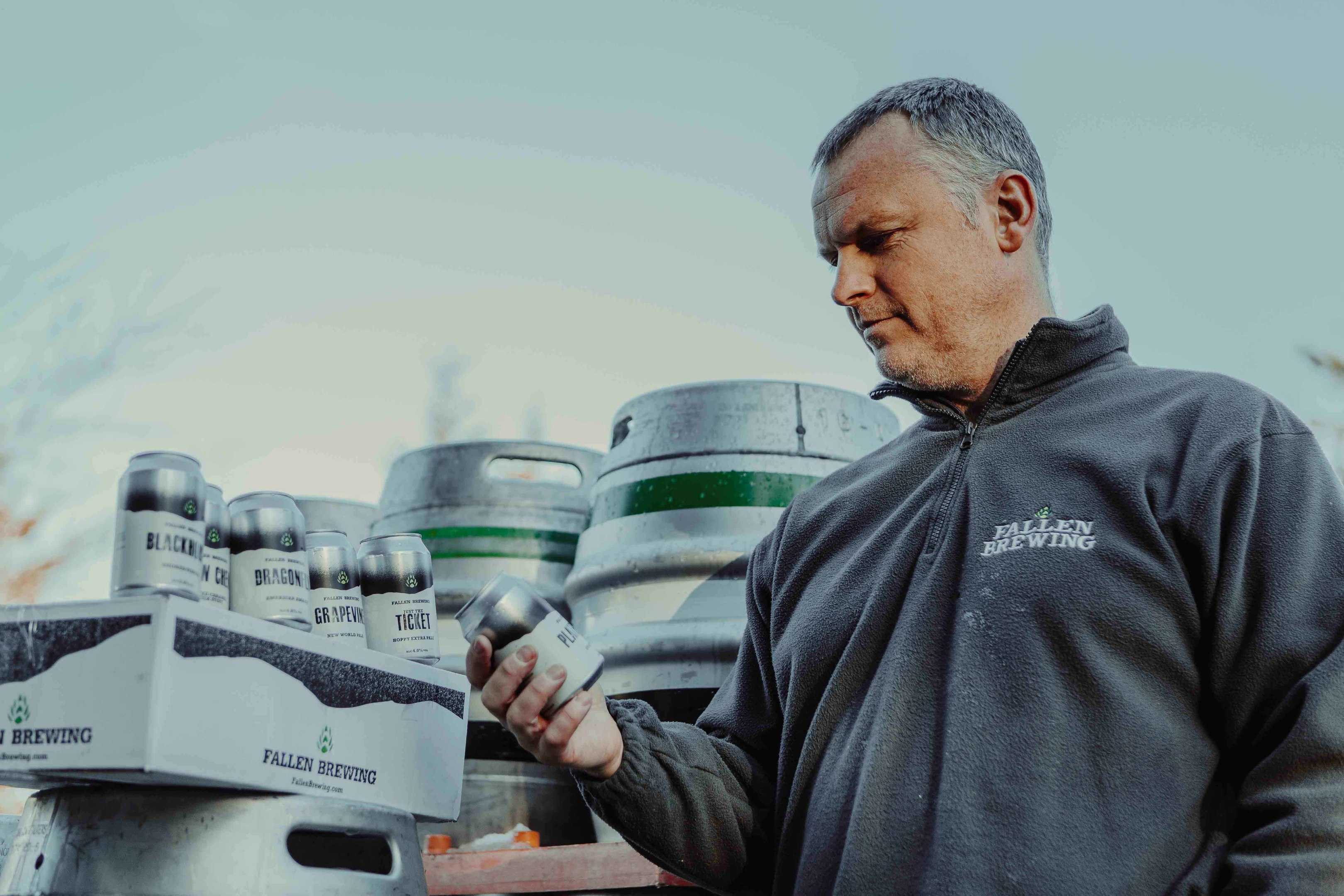 Paul Fallen inspects a can of beer from his new canning line.