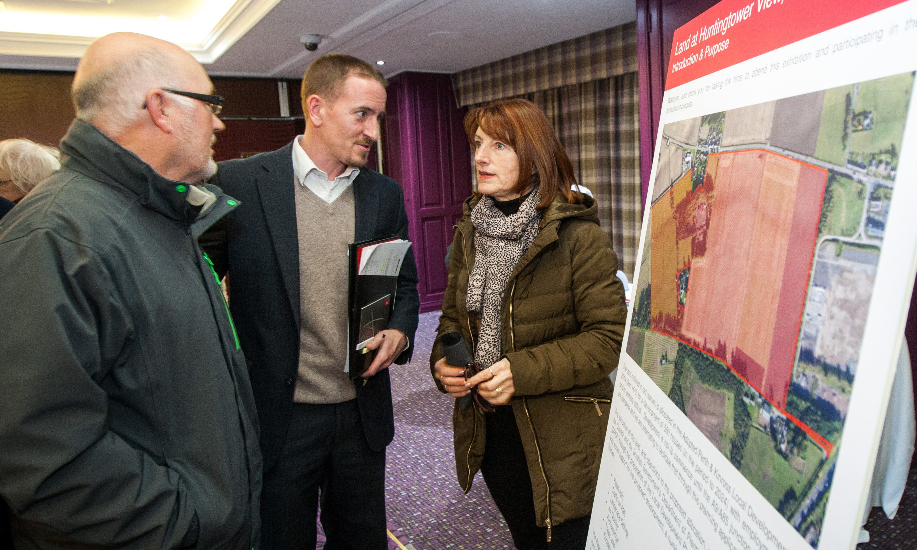 Strutt Parker hold an public exhibition regarding new homes planned for the area. Picture shows John Wright (centre, from Strutt Parker) alongside local residents Geoff and Viv Quigley.