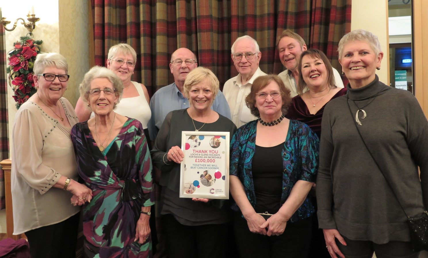 Dorothy Rodger, local fundraising manager for Cancer Research UK presents guests and staff at Lochs & Glens' Loch Tummel Hotel with a certificate to thank them for raising £100,000 to help beat cancer sooner.
