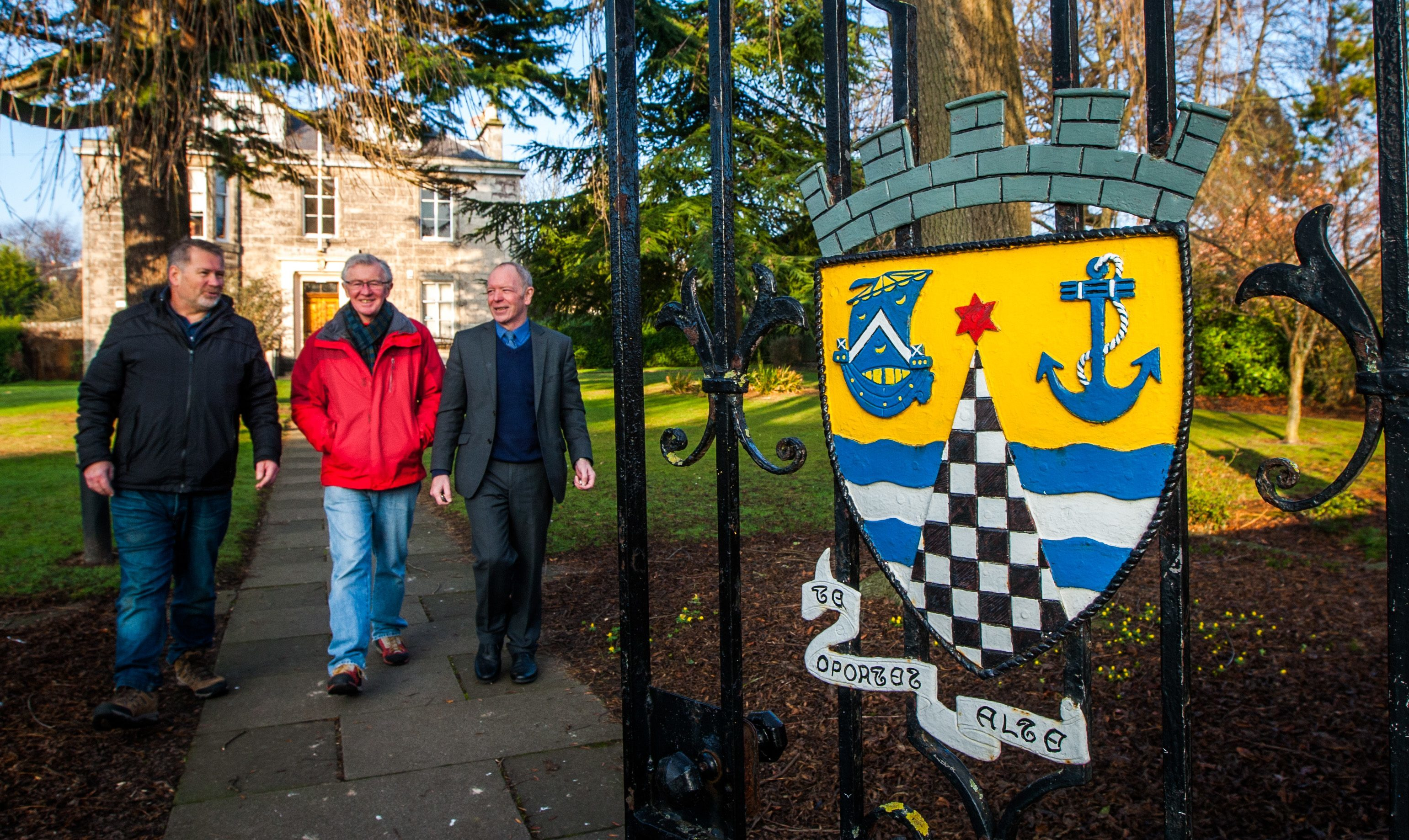 Derek Gray, Tony Gowland and Councillor Bill Connor, in the grounds of Burgh Chambers, alongside the crest of Tayport.