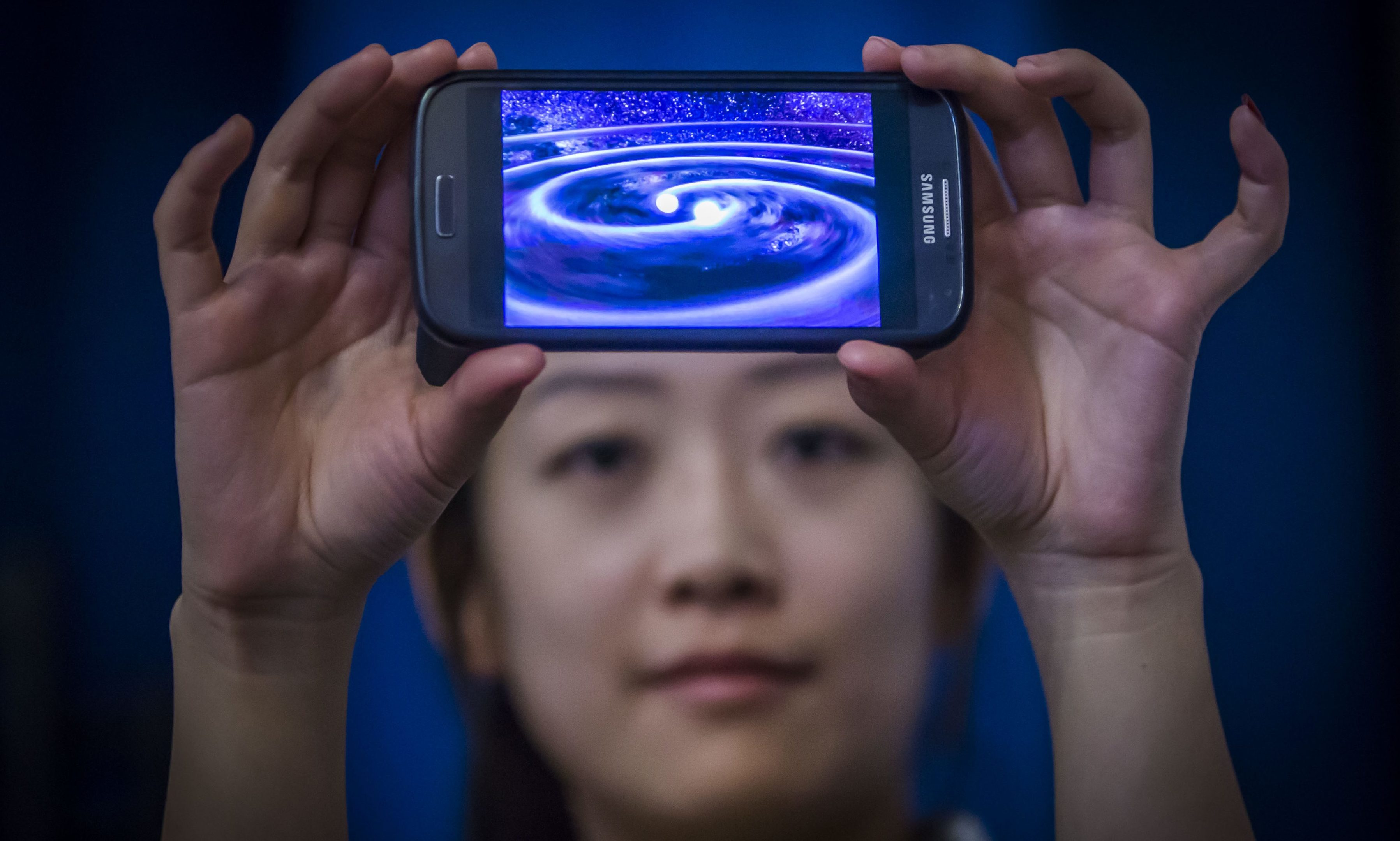 Student Muzi Li at the Institute of Gravitational Research at Glasgow University holding a phone that shows a computer simulation of gravity waves - ripples in spacetime - which have been detected by scientists a century after Albert Einstein predicted their existence.