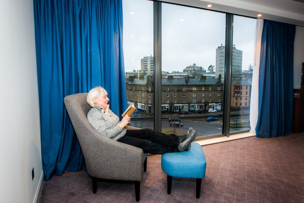 Duty manager Margaret Dempster relaxing by the floor to ceiling windows in one of the hotel rooms.