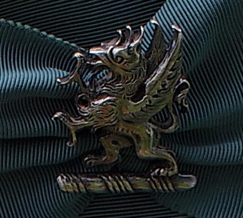 The cap badge, representing the family's 'Dancing Beastie' crest.
