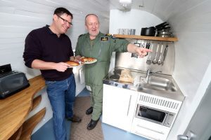 """Martyn Steedman (left) owner of a converted former Navy Sea king MK6 helicopter has a Cornish Pastie with Lt Cdr Andy Murray (who flew the helicopter many times when it was in active duty at RNAS Culdrose) in the kitchen area of  the converted  helicopter during a visit to see it at its new base at Mains Farm Wigwams  in Thornhill.  PRESS ASSOCIATION Photo. Picture date: Friday March 24, 2017. Lieutenant Commander Andy """"Tank"""" Murray and his crew stopped off to visit the Sea King near Stirling as they flew north to take part in a training exercise. See PA story AIR SeaKing. Photo credit should read: Andrew Milligan/PA Wire"""