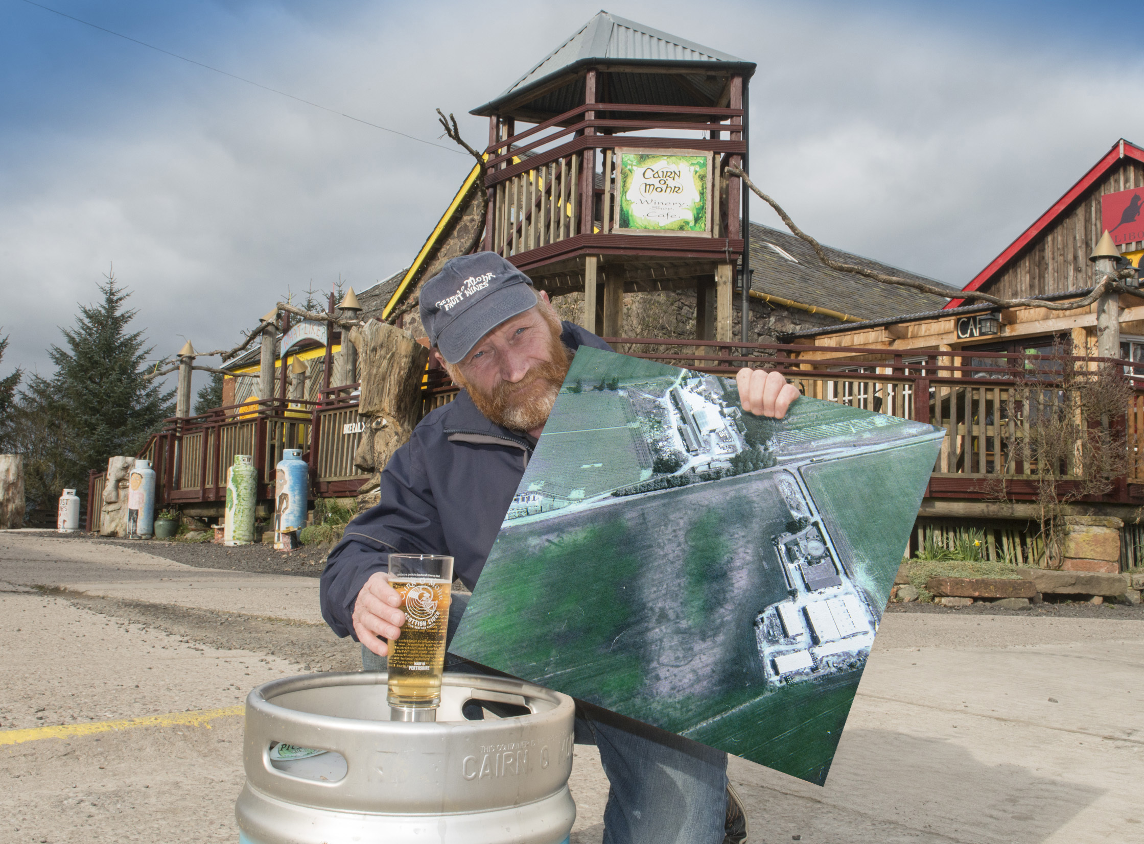 Ron Gillies, winery owner, pictured with the new draught cider and the aerial photograph showing the outline of the prehistory Pictish settlement.