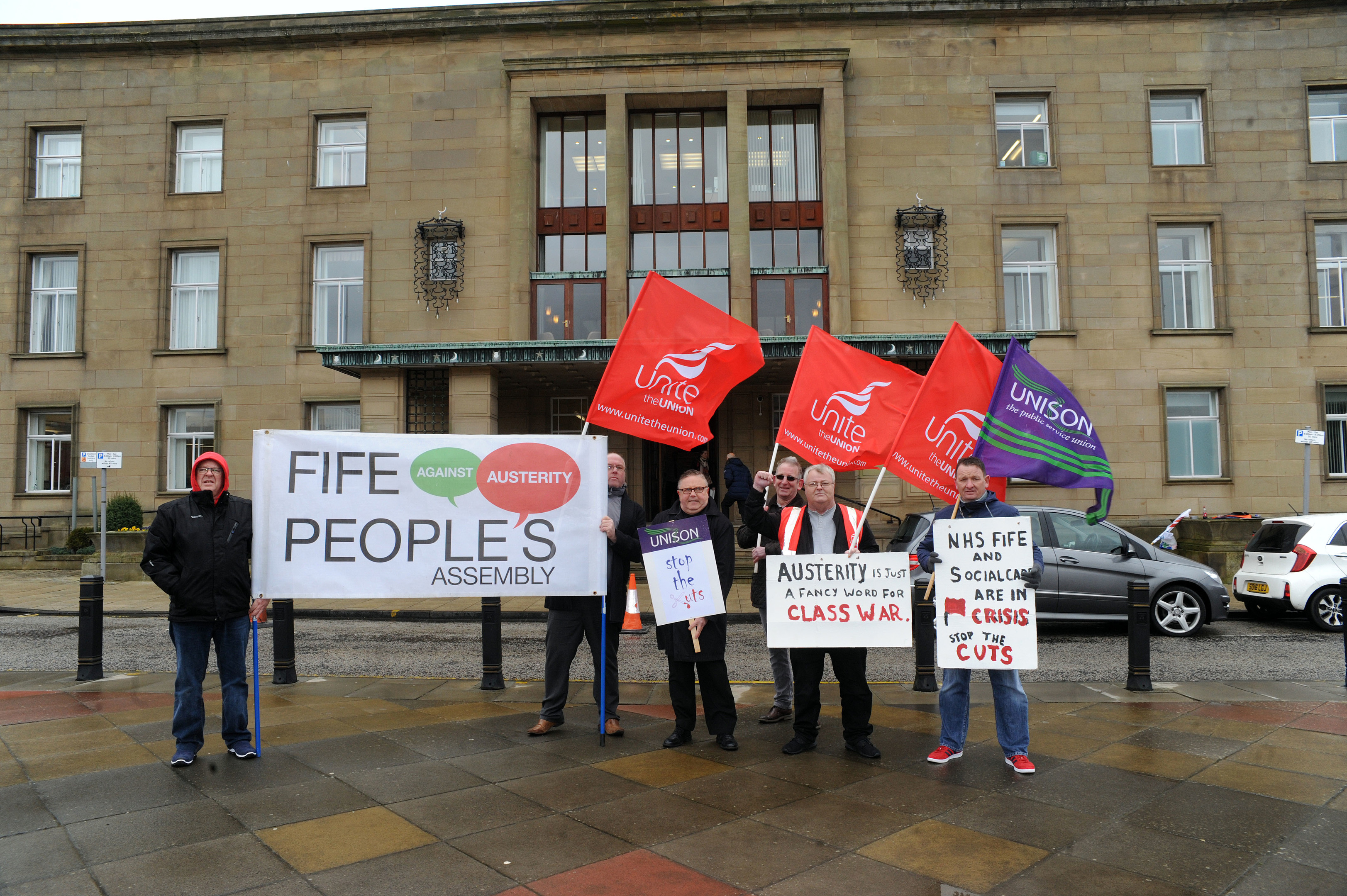 A small group of anti-cuts protesters staged a noisy protest outside the meeting.