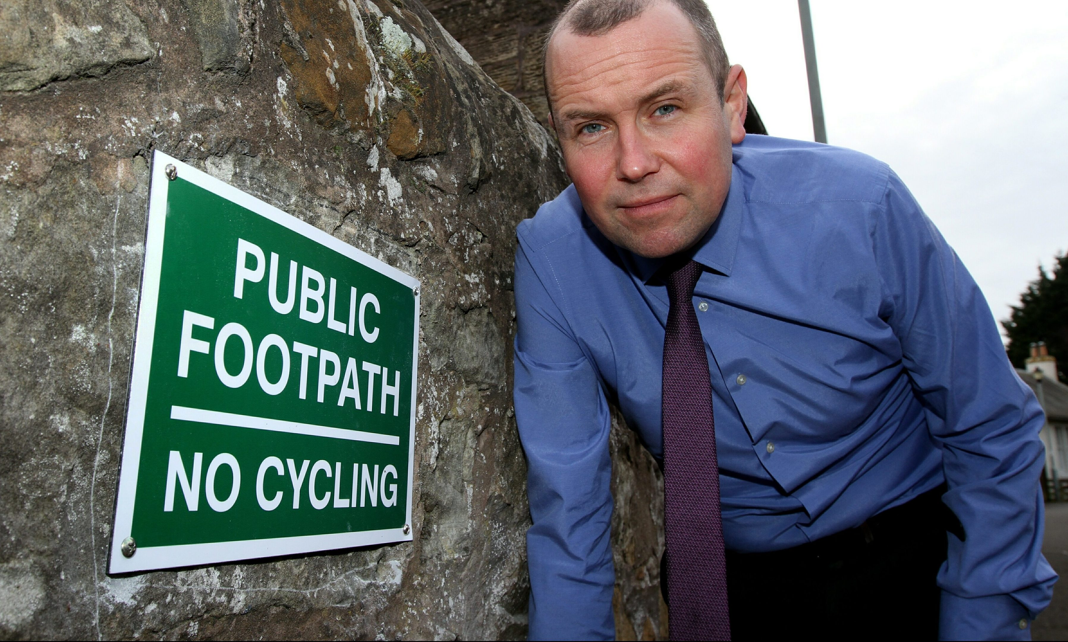 Brian Thomson beside the unauthorised sign.