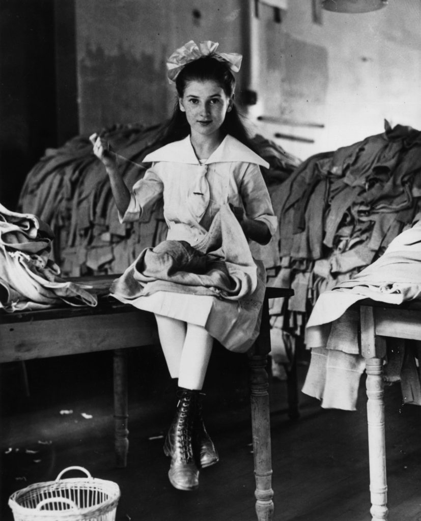 A young American girl repairing army uniforms during the First World War. (Photo by Keystone/Getty Images)