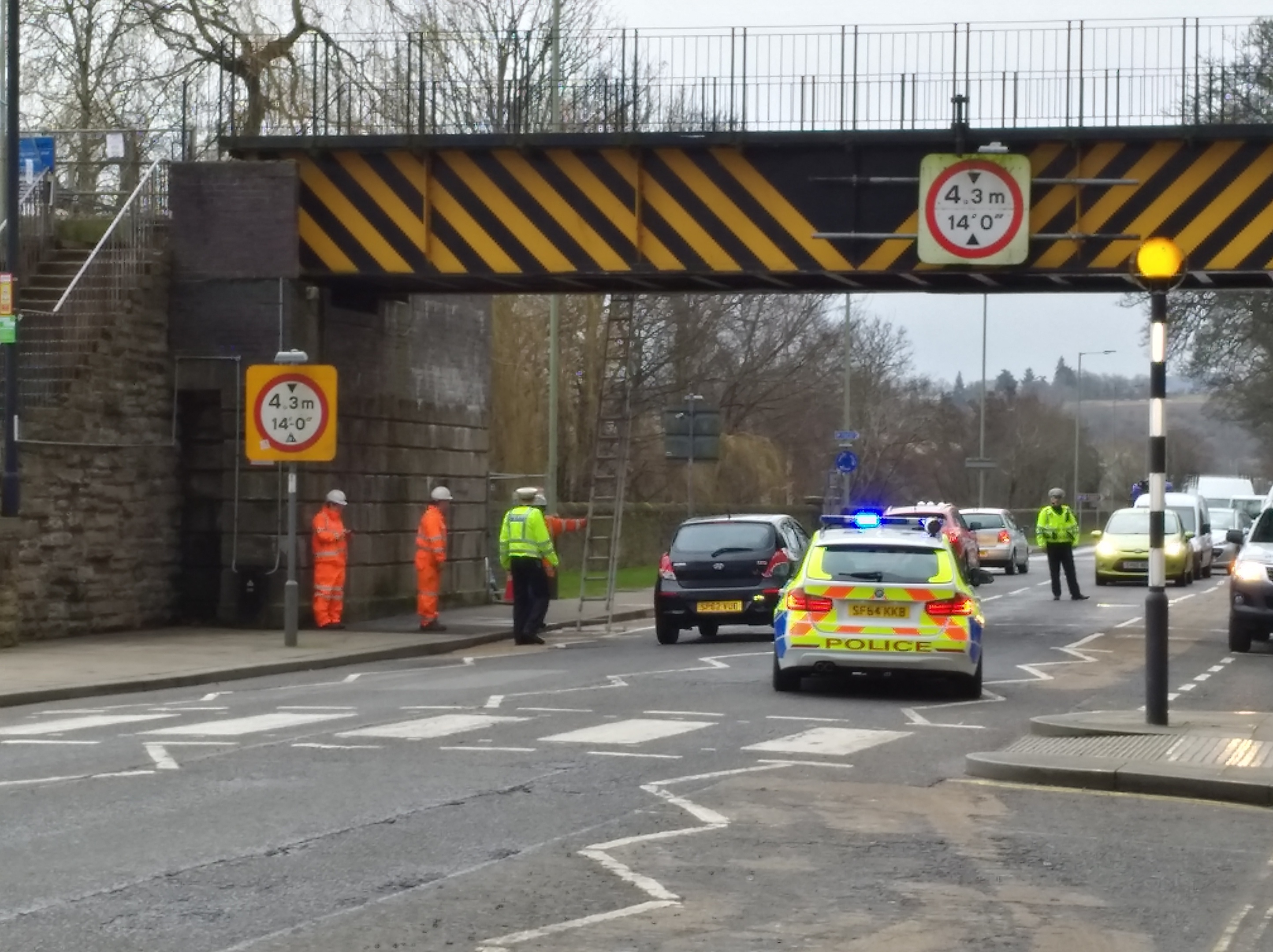 Police officers direct traffic as engineers assess damage to the bridge.