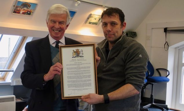 Sir Andrew Cubie presents Anstruther Lifeboat coxswain Michael Bruce with a chairman's letter of thanks.