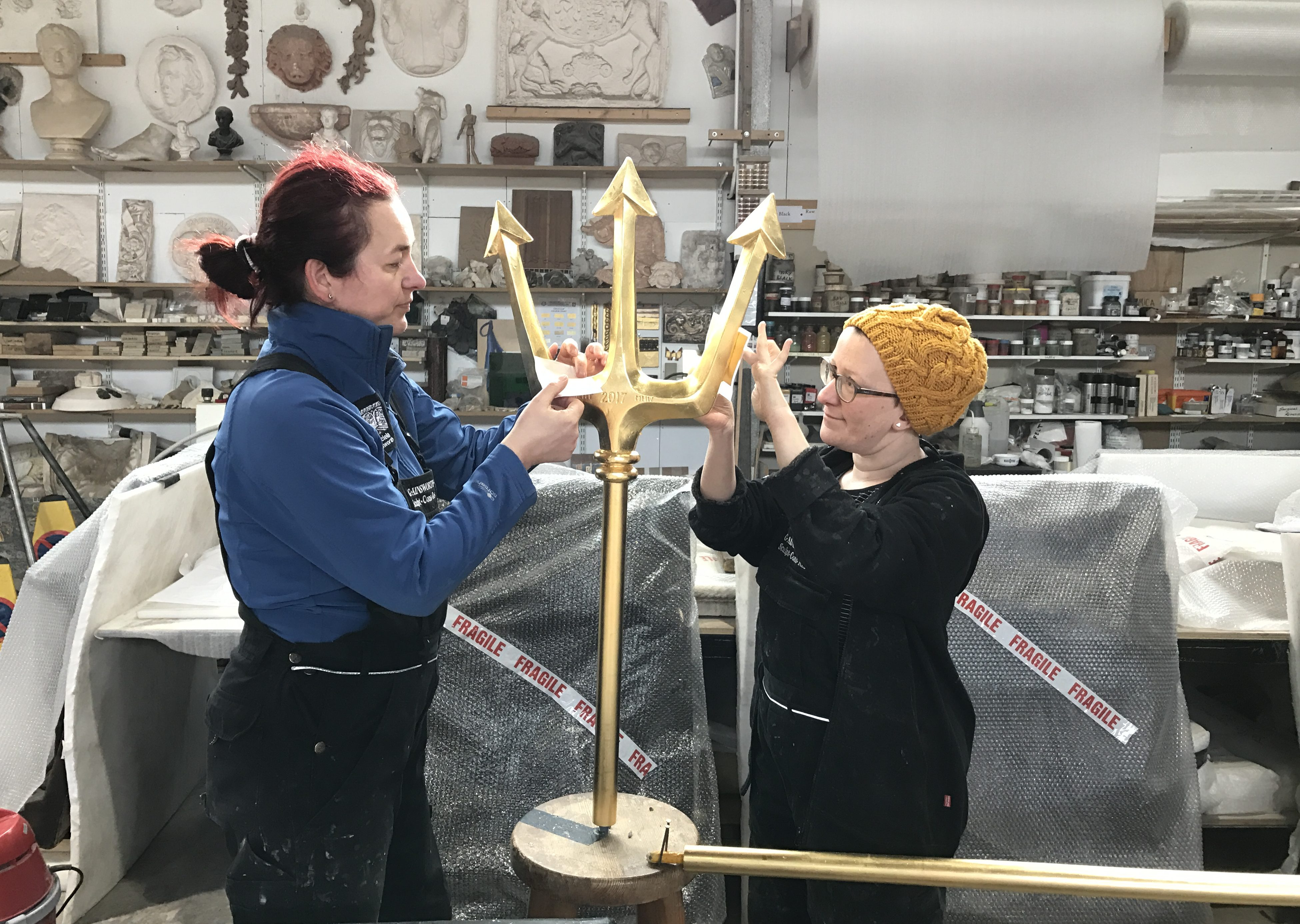 The new trident being gilded by Csilla Karsay and Ellie King of Graciela Ainsworth Sculpture Conservation.