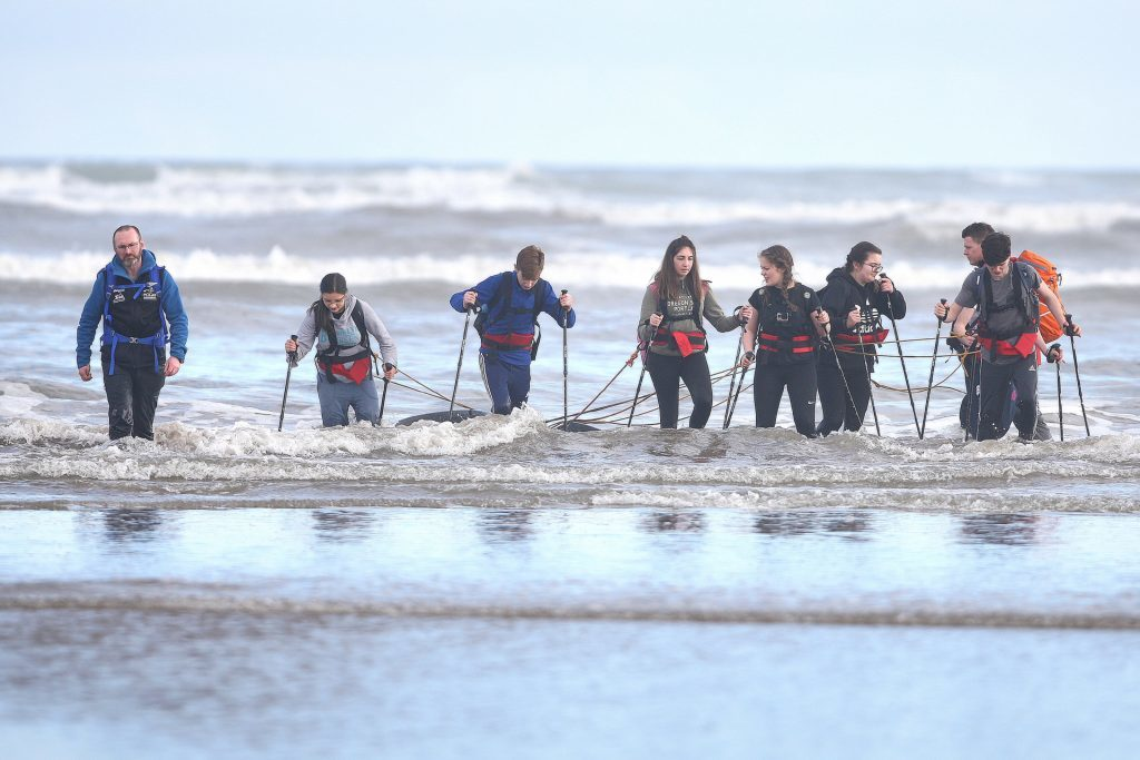The Polar Academy team walking into the chilly North Sea with their tyres.
