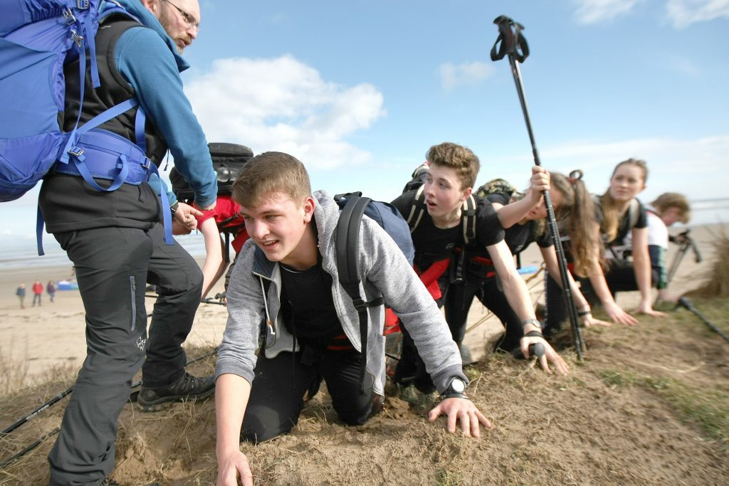 """Craig Mathieson instructs the teenagers to do """"polar press ups"""" on the beach!"""
