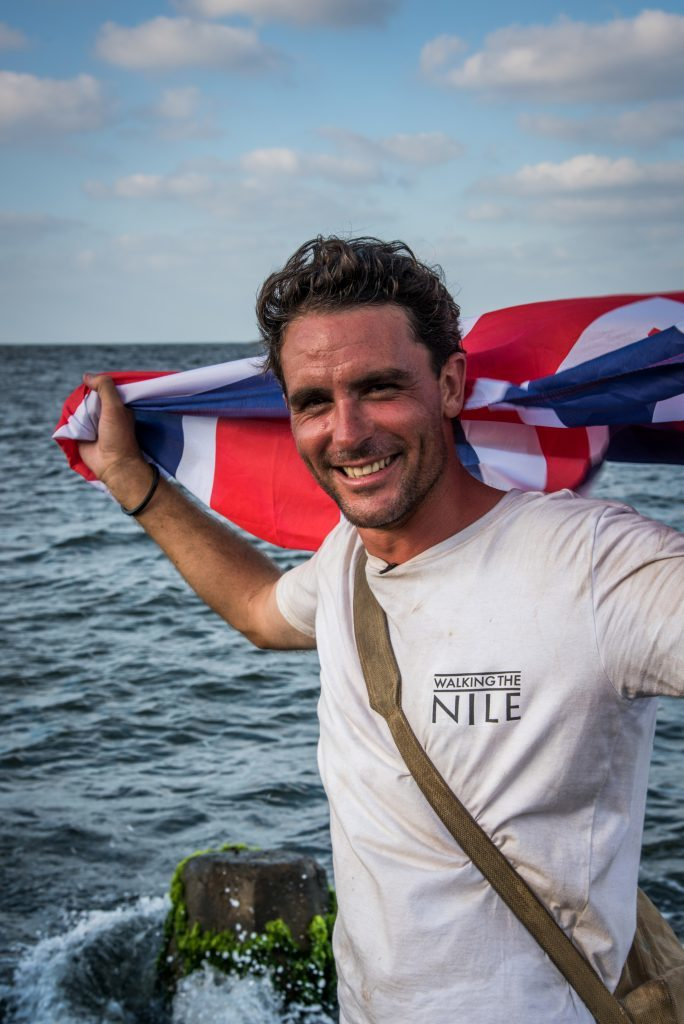 Lev hold the Union flag aloft as he completes his epic journey of walking the Nile.