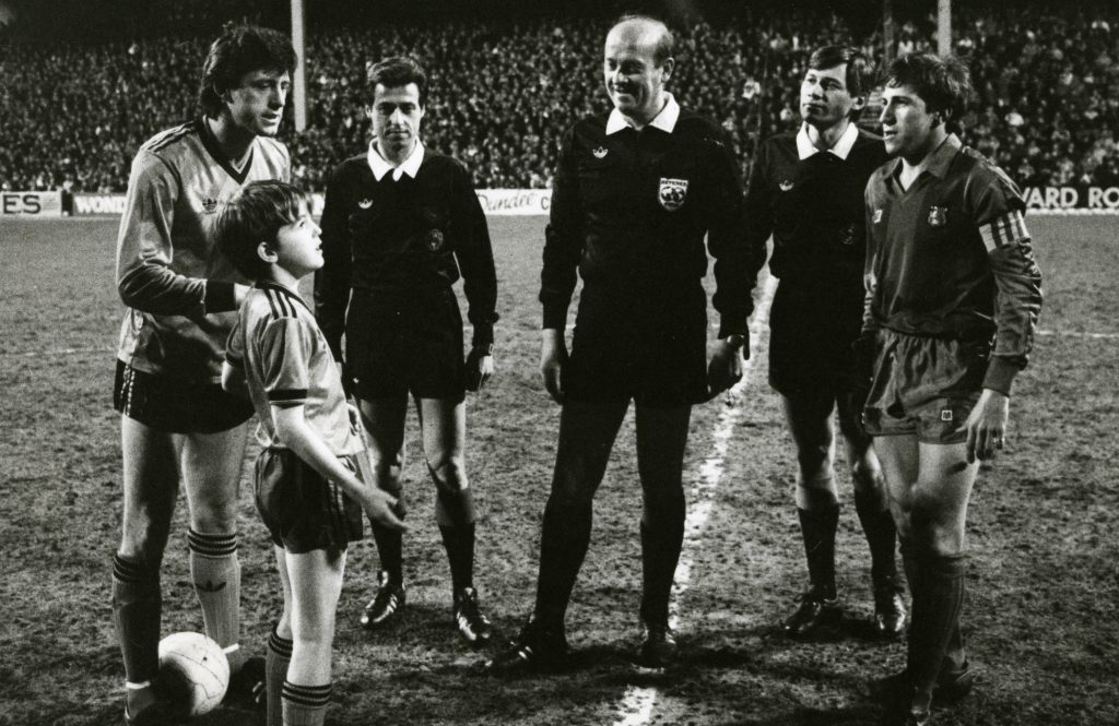 United Mascot at Barcelona Game. Photograph showing the match officials with each teams captain as United mascot Scott Mitchell stands in awe. 4 March 1987.