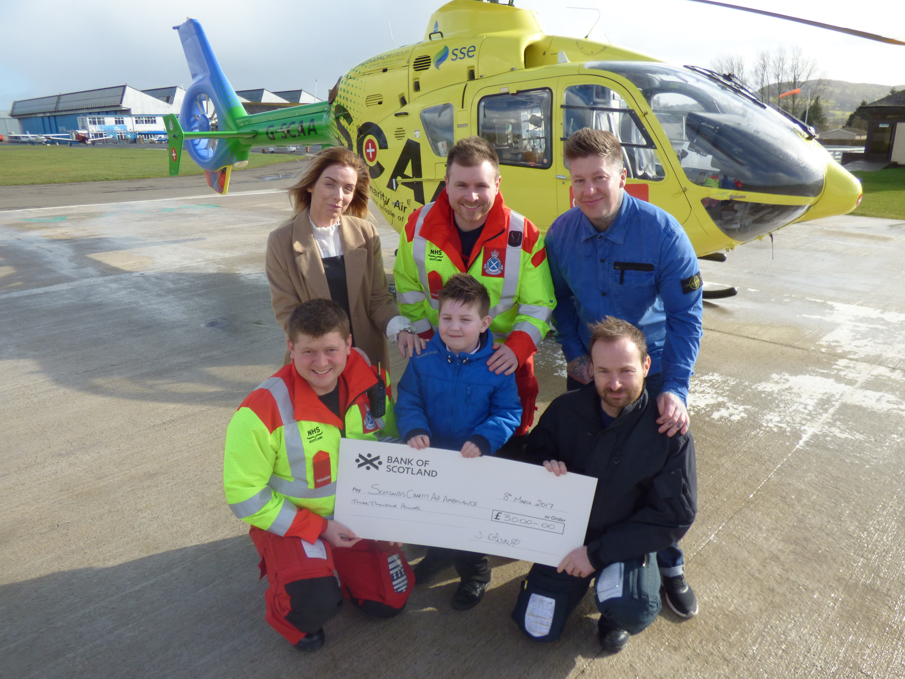 Six-year-old Leon Edwards adds his thanks to SCAA crew as he hands over the cheque with mum Sara and dad Steven to paramedics Richard Forte (back) and Graeme Hay and pilot John Stupart.