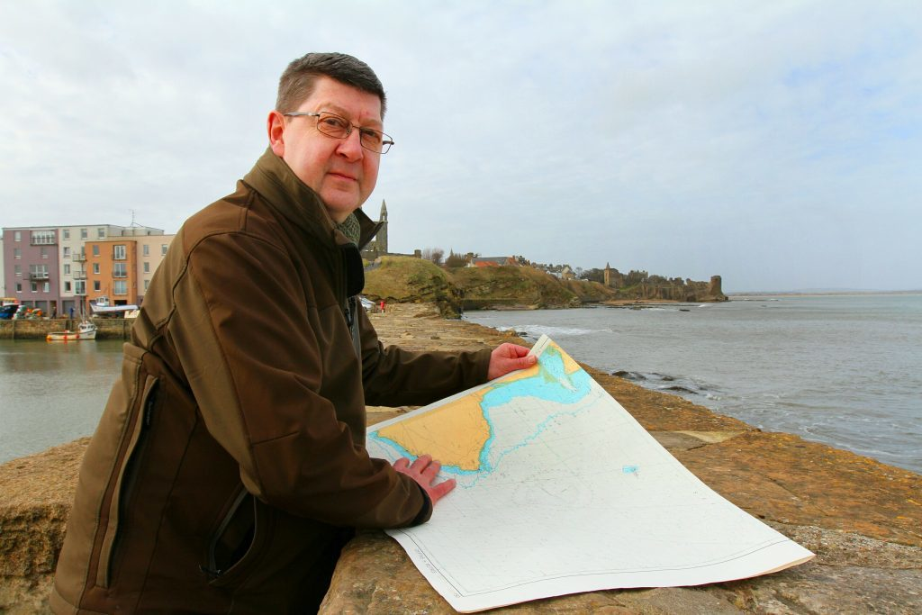Maritime archaeologist Neil Dobson from St Andrew with a sea chart of St Andrews Bay