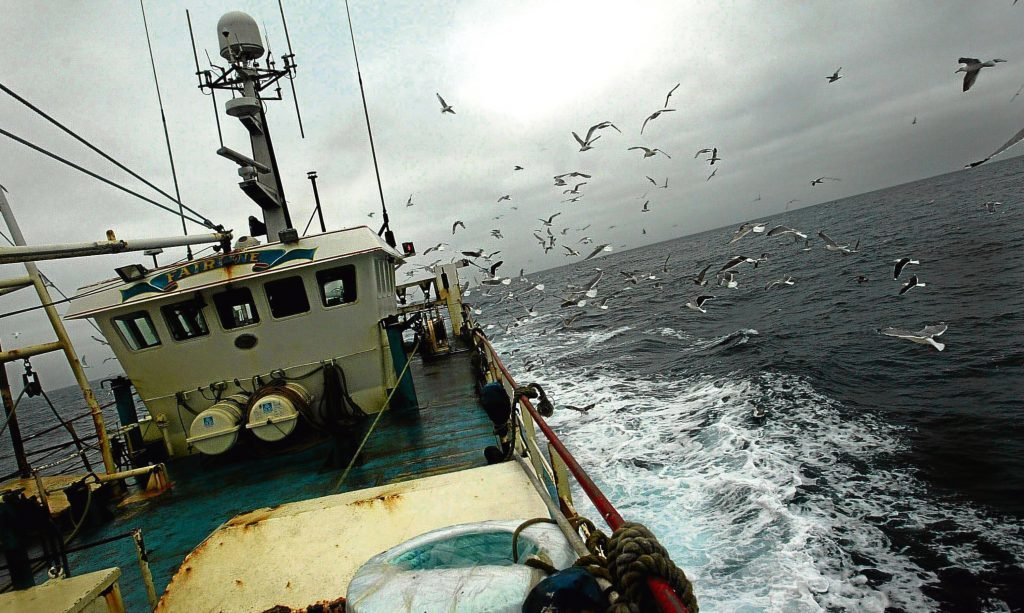 A Scottish fishing boat leaves port for the North Sea fishing grounds.