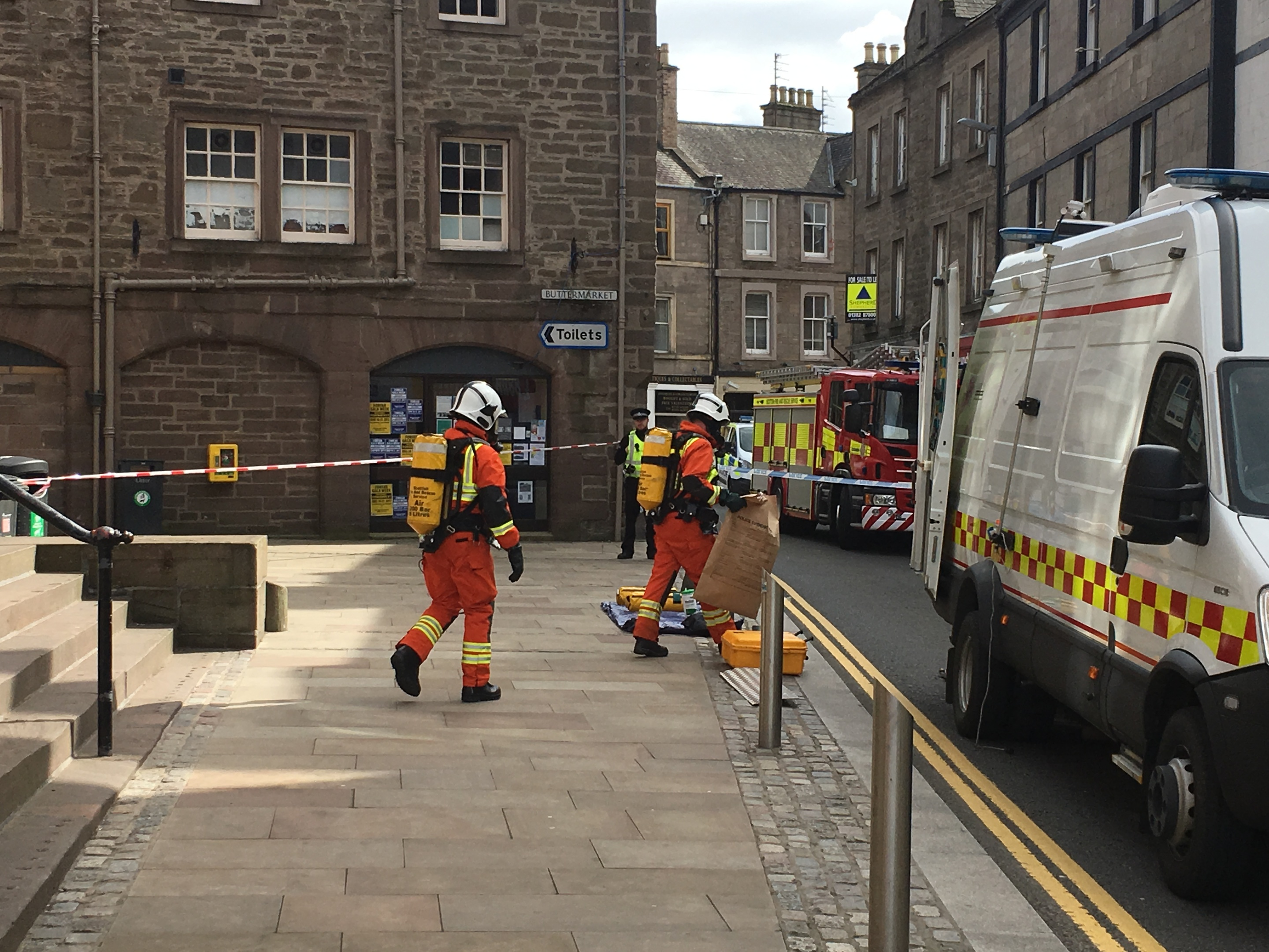 Specialist fire fighters leaving Angus Council offices with the suspect package in a brown evidence bag