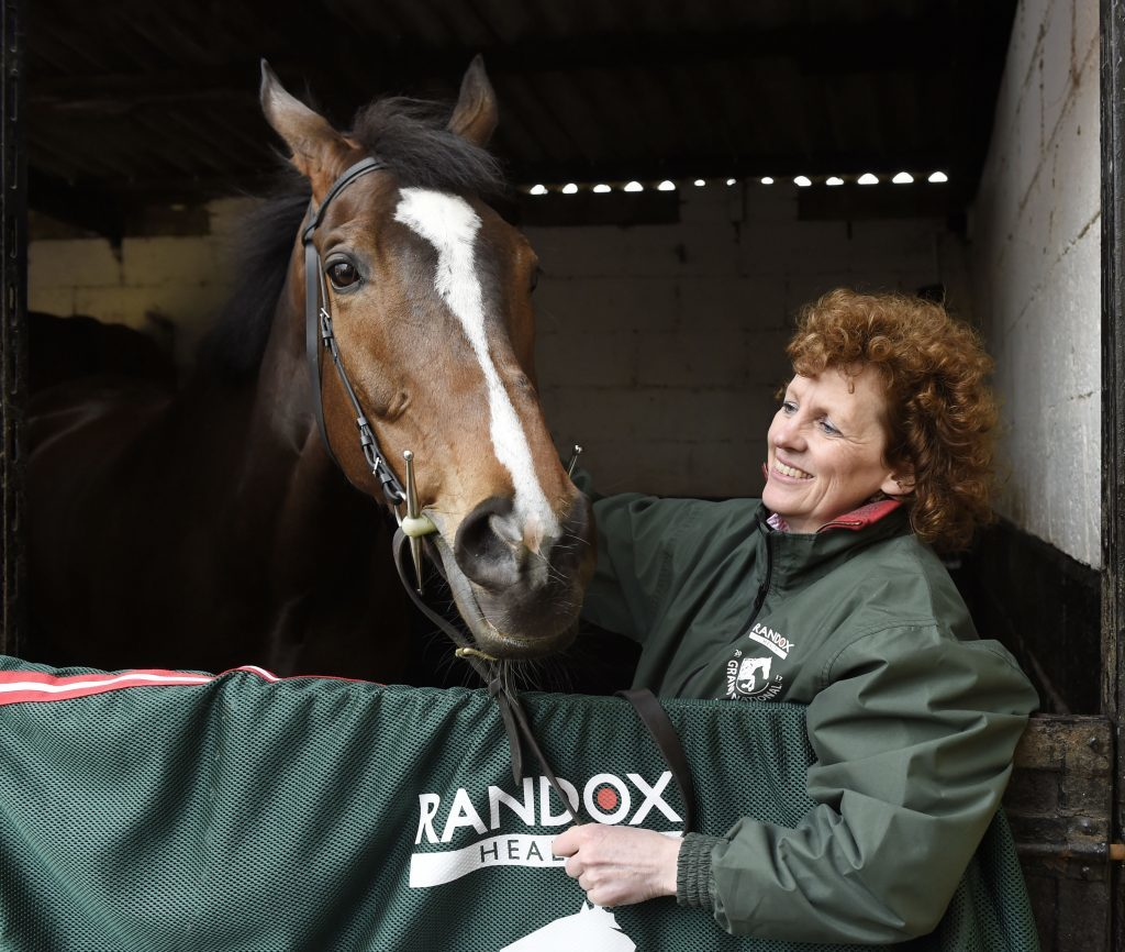 Grand National winner One For Arthur pictured with trainer Lucinda Russell at her yard.