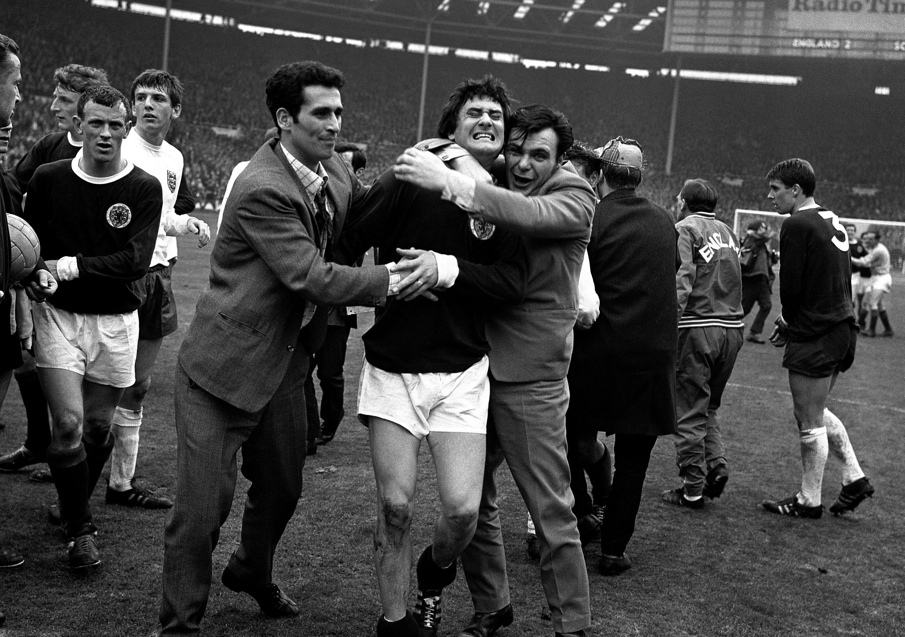 The squeeze makes itself felt for Scotland's Jim Baxter (centre), enthusiastically hugged by overjoyed fans who invaded the Wembley Stadium pitch after England had been beaten 3-2 in their football match against Scotland on April 15, 1967