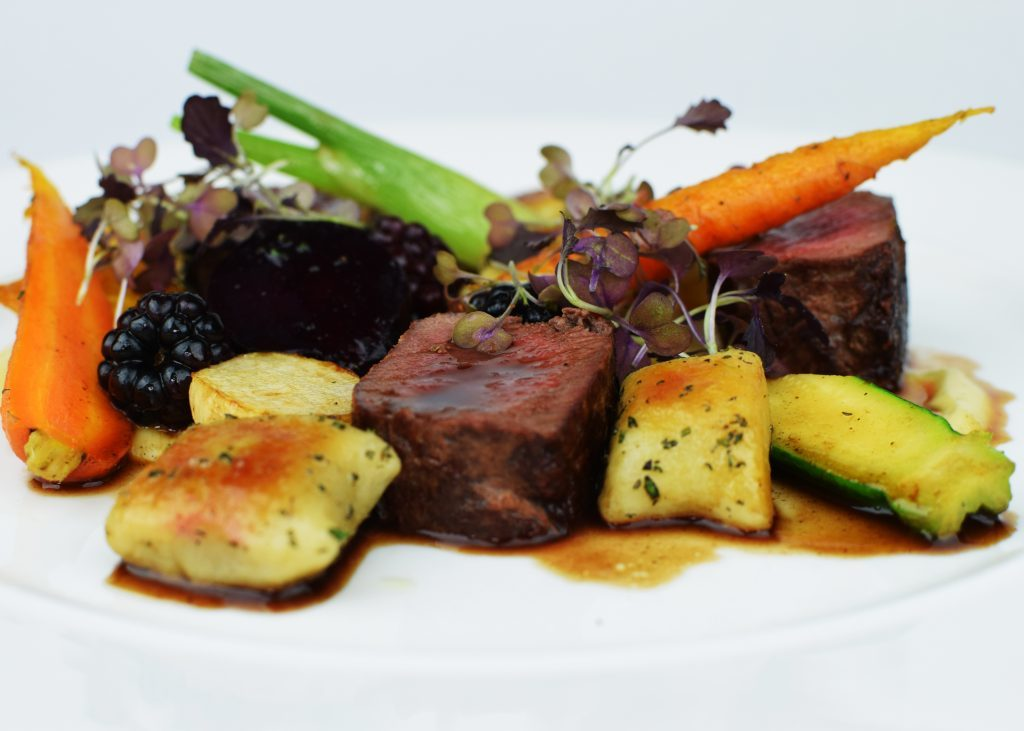 Venison loin with rosemary gnocchi, roast baby vegetables & blackberry jus