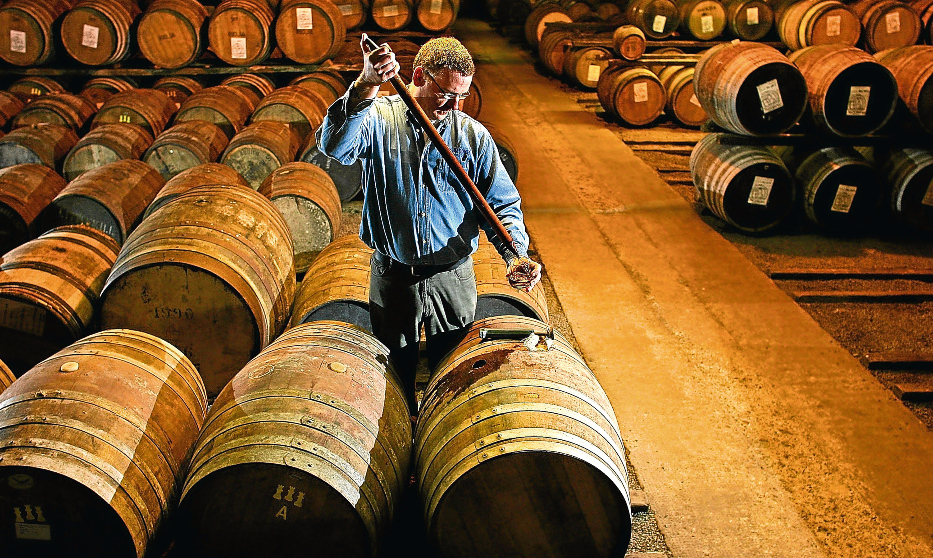 A whisky sample is taken from a cask at  Bruichladdich in Islay.