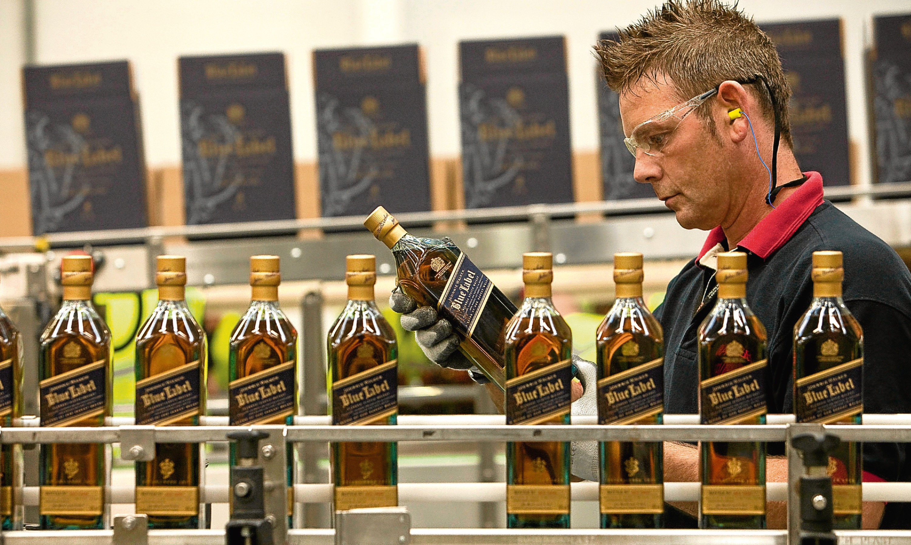 An employee checks a bottle of Johnnie Walker Blue Label whisky on the production line at Diageo's bottling plant in Leven.