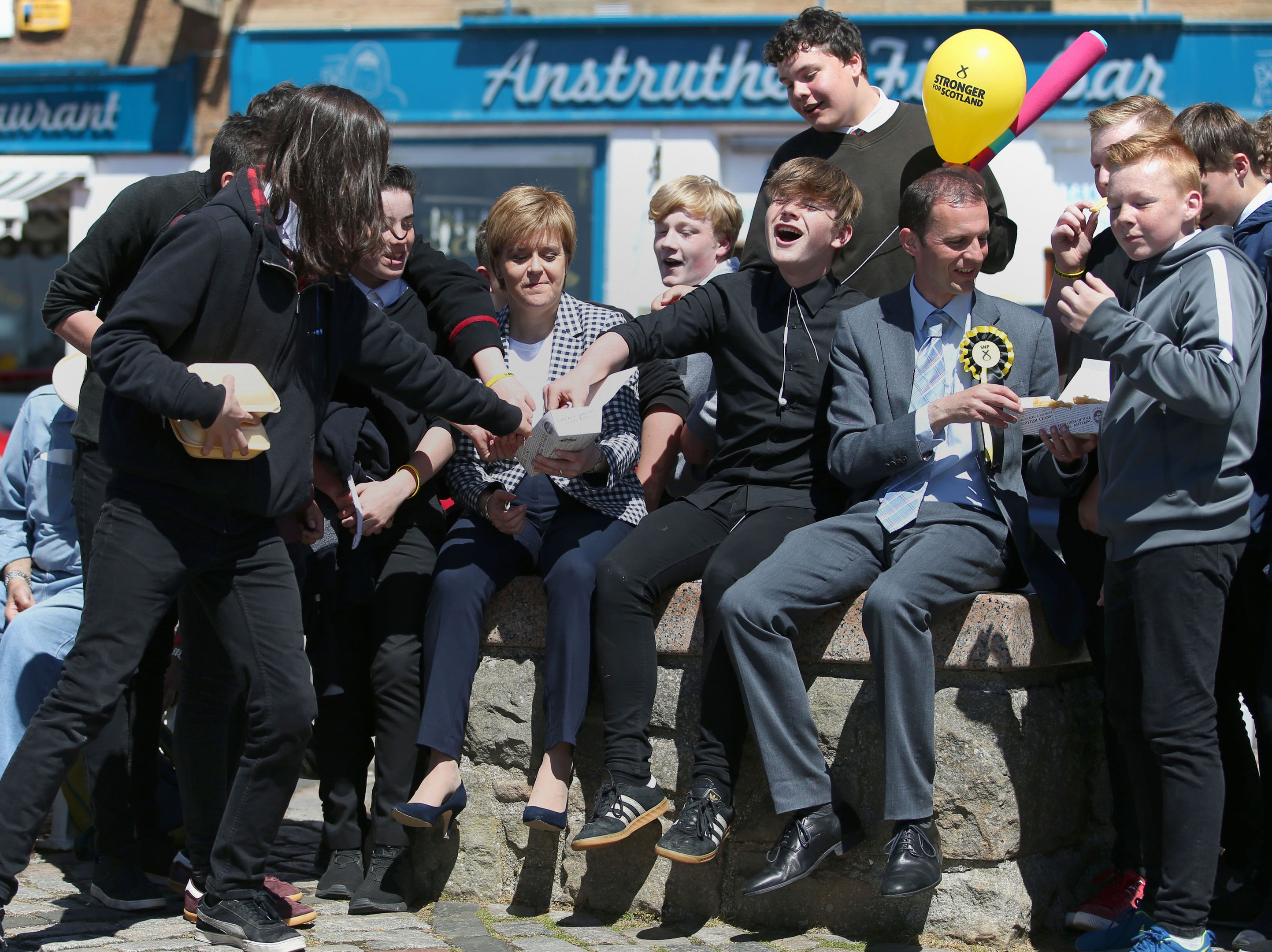First Minister Nicola Sturgeon and the SNP's local candidate Stephen Gethins share chips with school children during a General Election campaign visit to Anstruther, Fife.