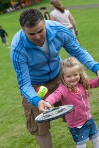 Holly Slattey has some tennis coaching from dad James at the Fresh Air Festival,