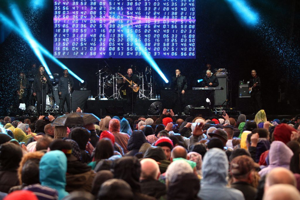 UB40 on stage as fans enjoying the show in rain and shine.