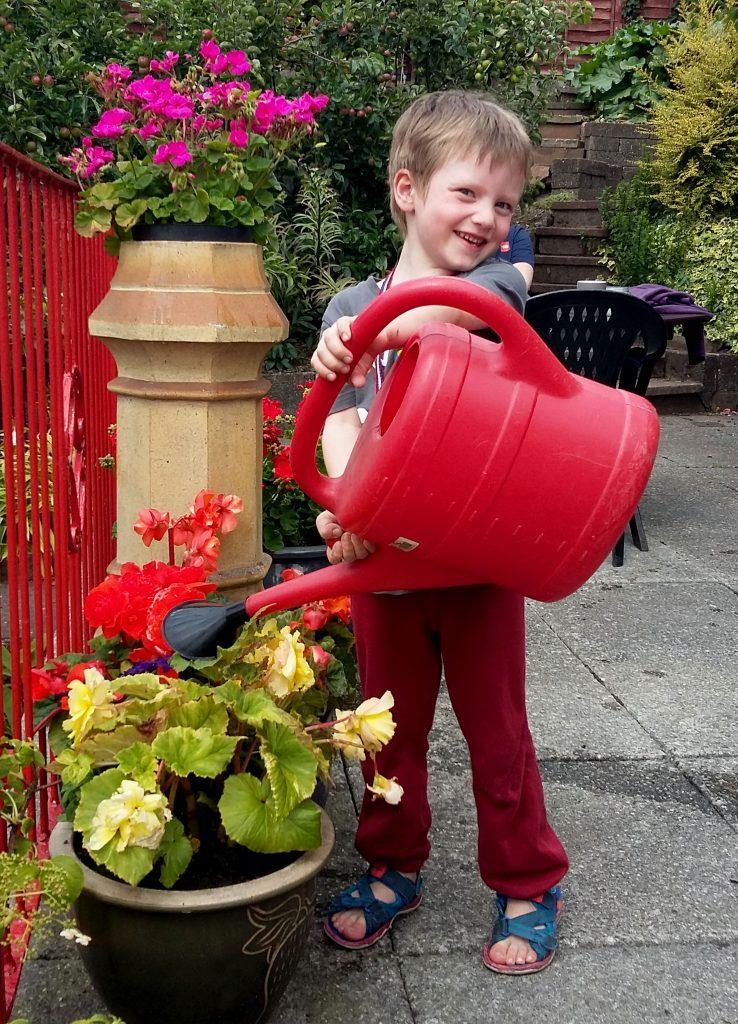 Luke watering the summer flowers