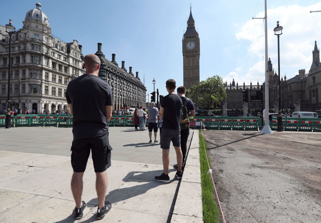 People observe a minute's silence in Parliament Square, London.