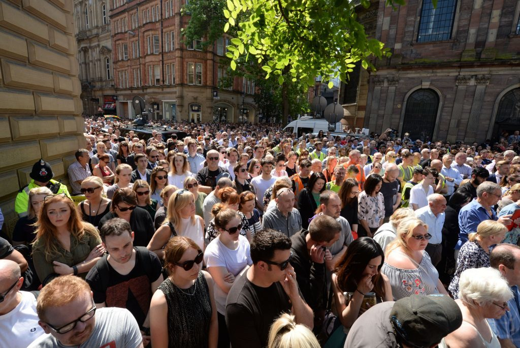 People observe a minute's silence in St Ann's Square, Manchester.