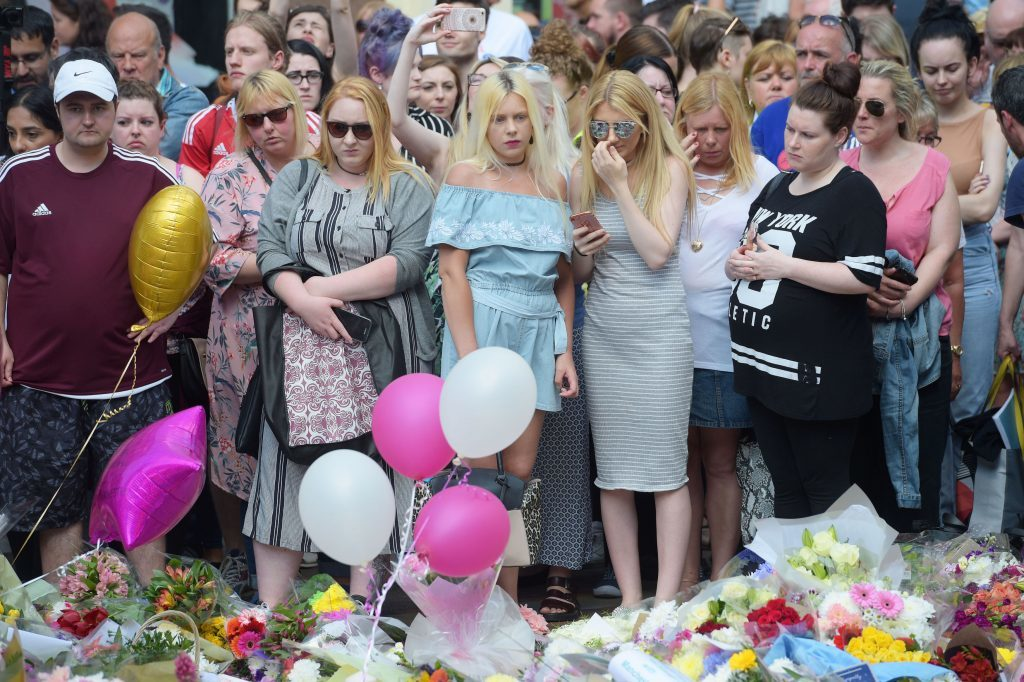 People look at floral tributes after a minute's silence in St Ann's Square, Manchester.