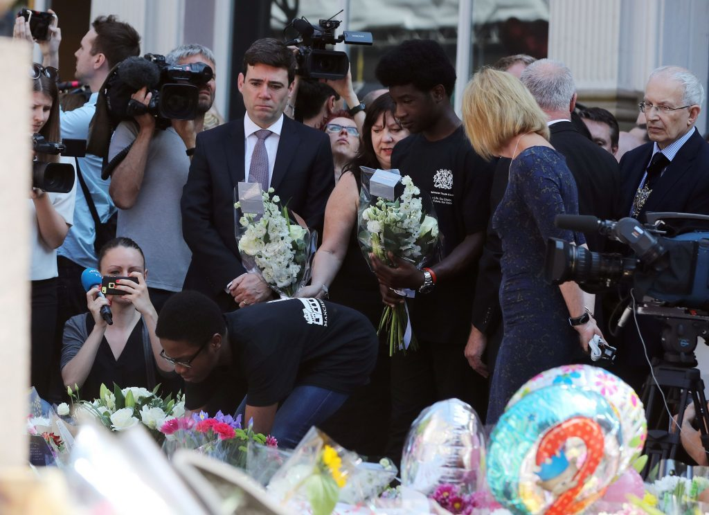 Mayor of Greater Manchester Andy Burnham lays flowers after a minute's silence in St Ann's Square, Manchester.