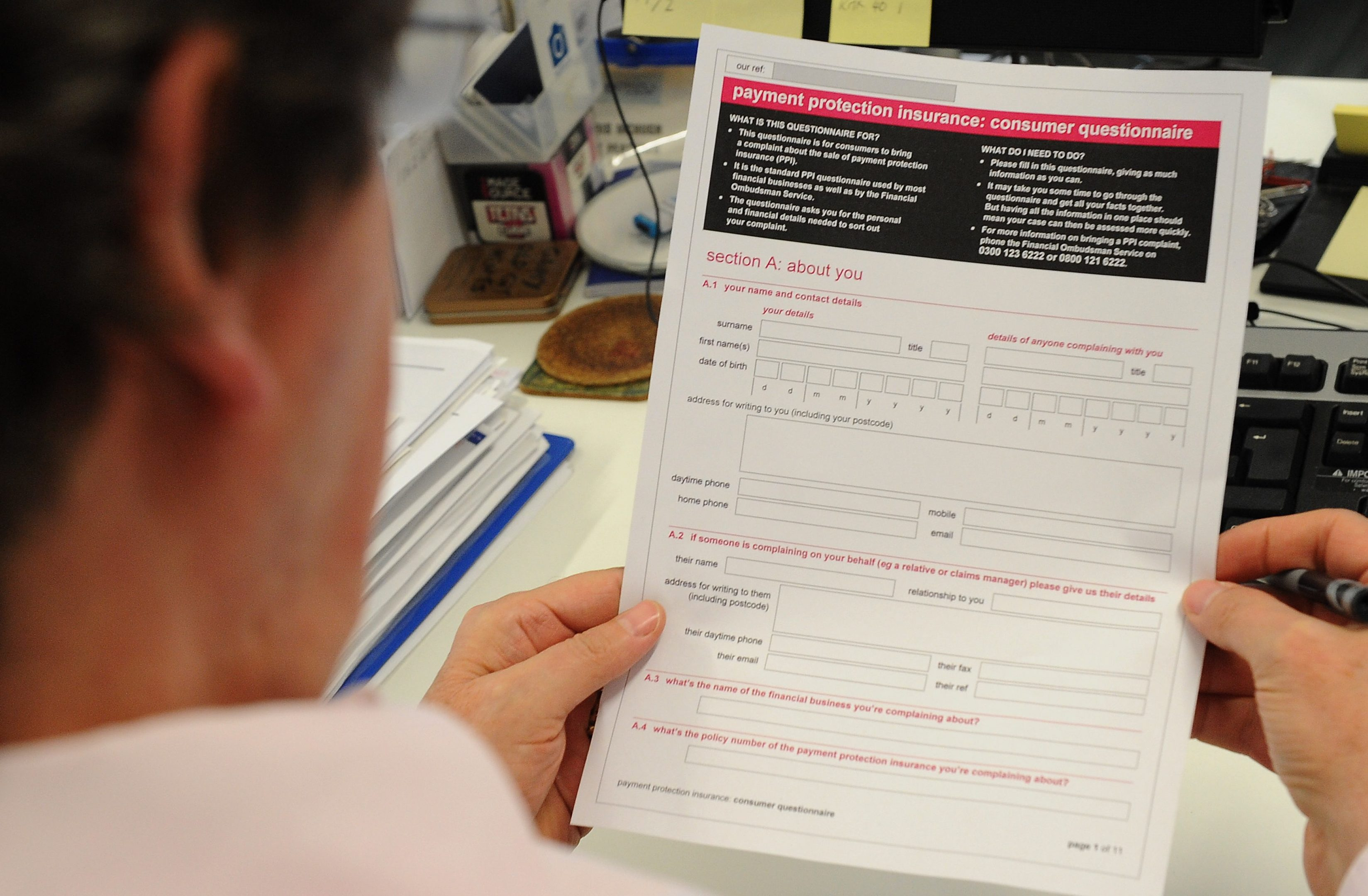 Man looking at a Payment Protection Insurance (PPI) claim form.