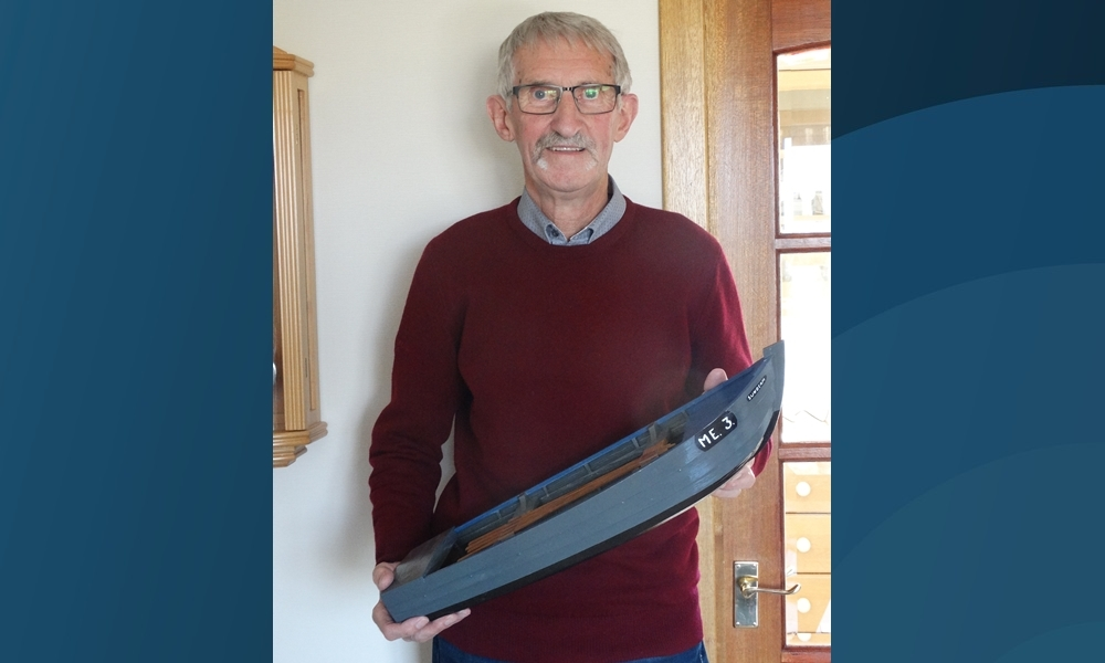 Tom Easton holding a miniature version of one of his salmon fishing cobles.
